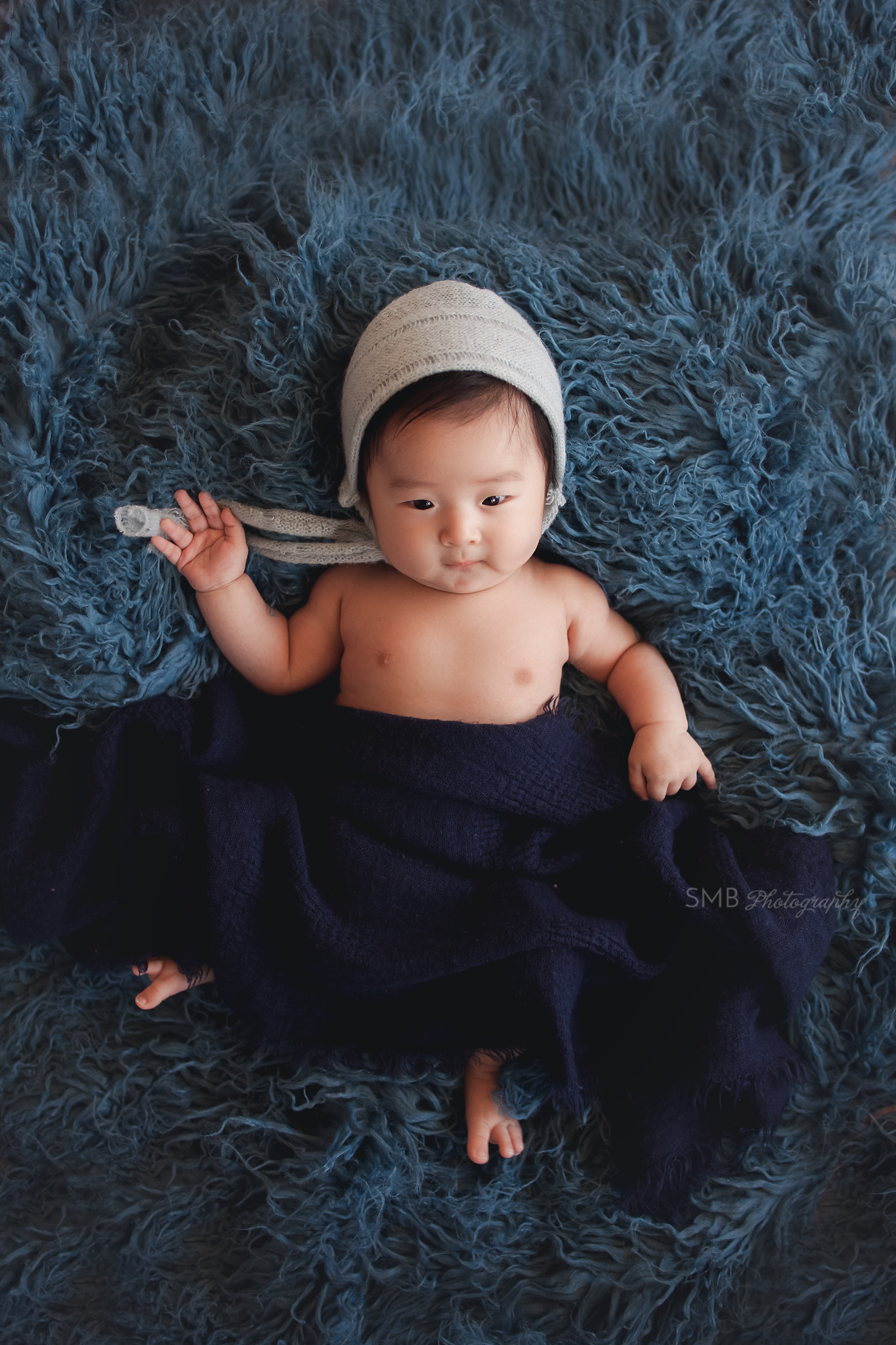 Baby boy wearing blue bonnet on dark blue flokati