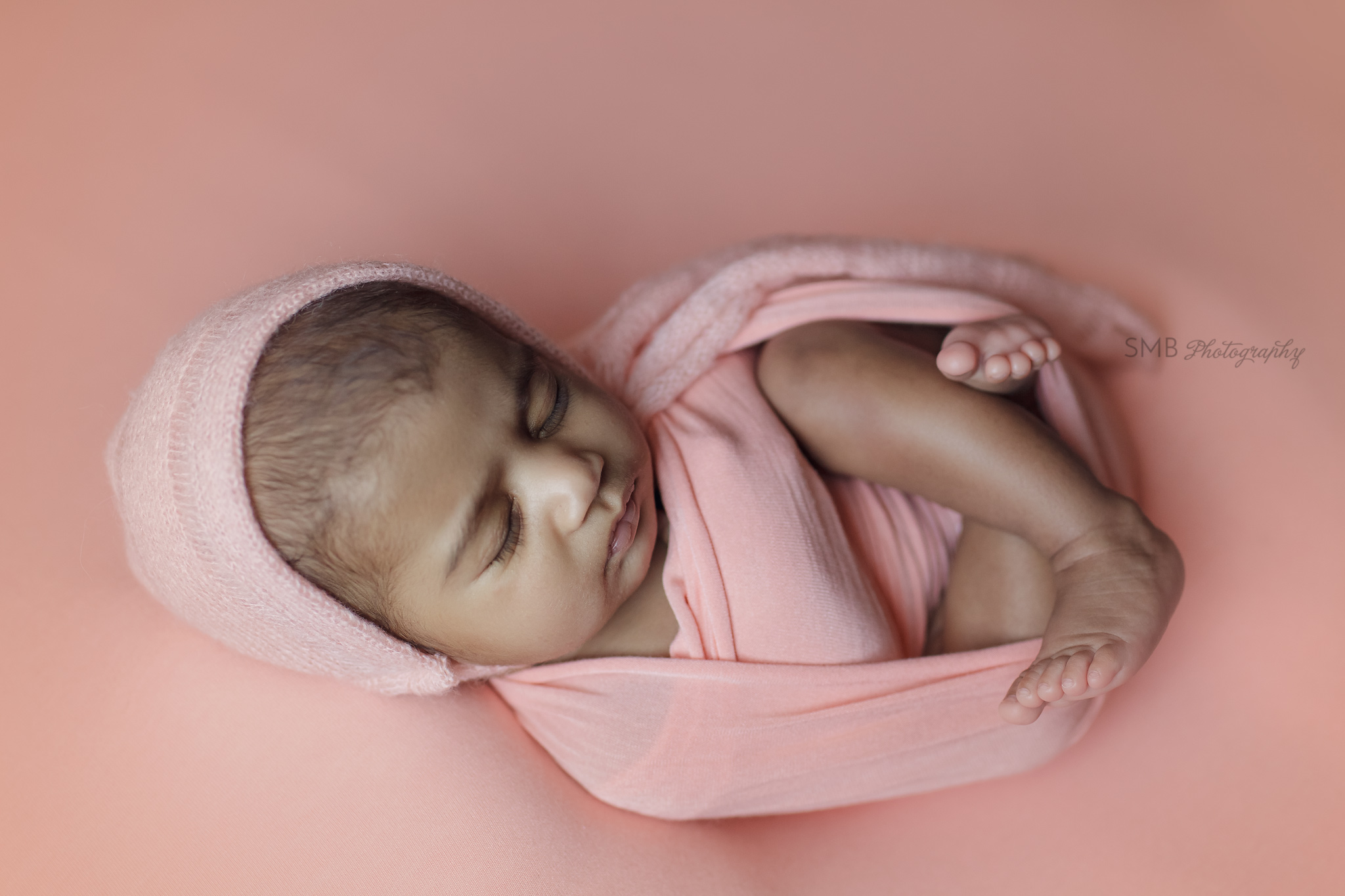 Newborn girl wrapped on peach backdrop, with feet out.