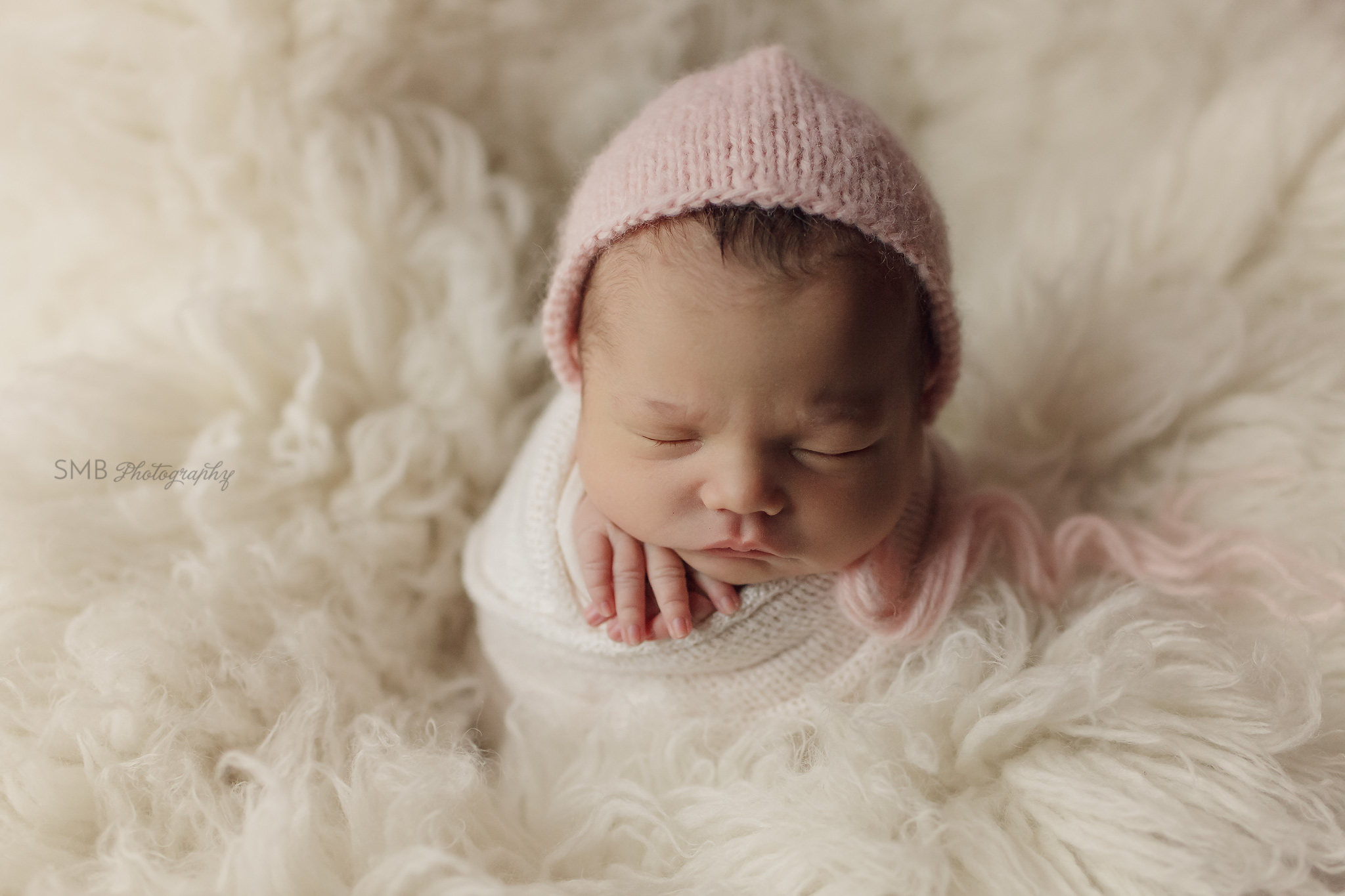 Newborn girl on cream flokati