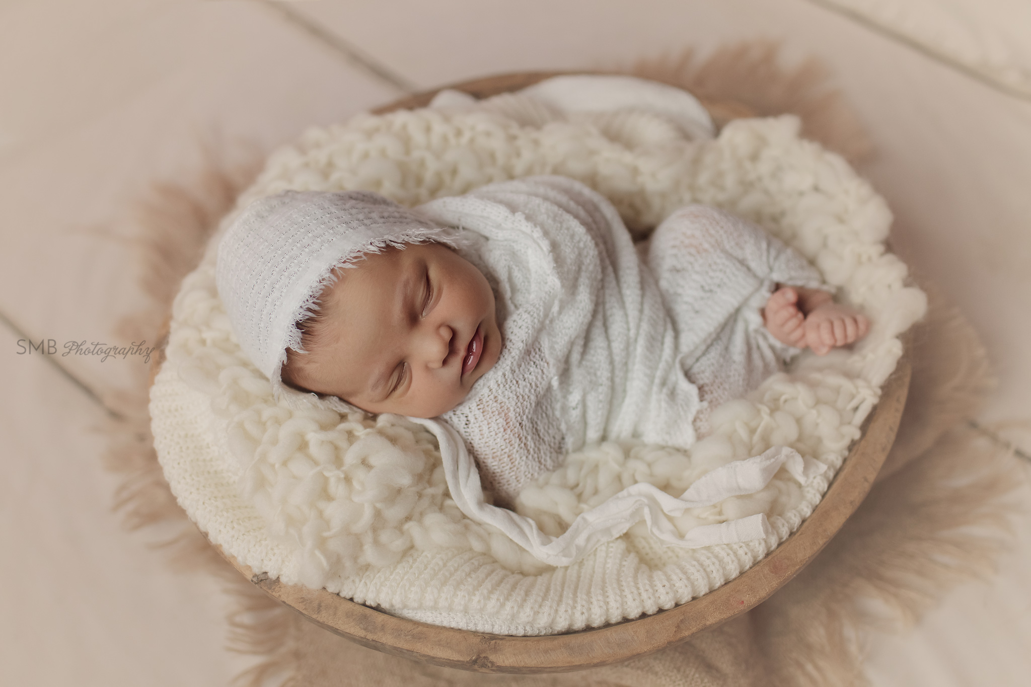 Baby wrapped in cream in a large wood bowl