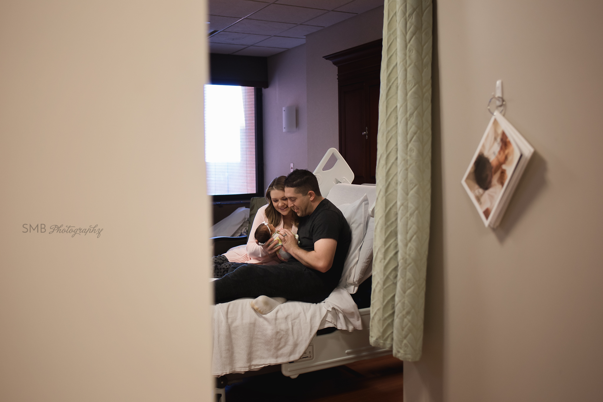 Mom, Dad and newborn baby girl in hospital bed