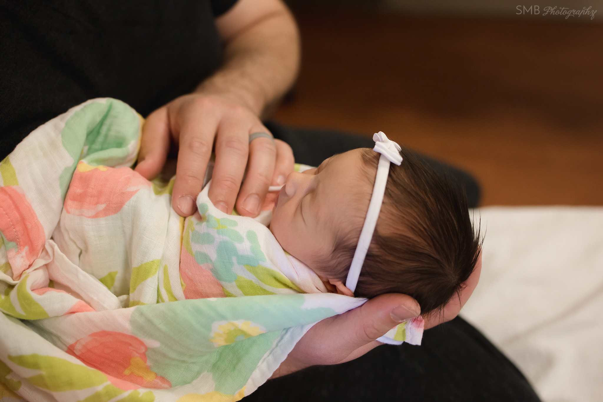 Newborn baby girl wrapped in Dads hands