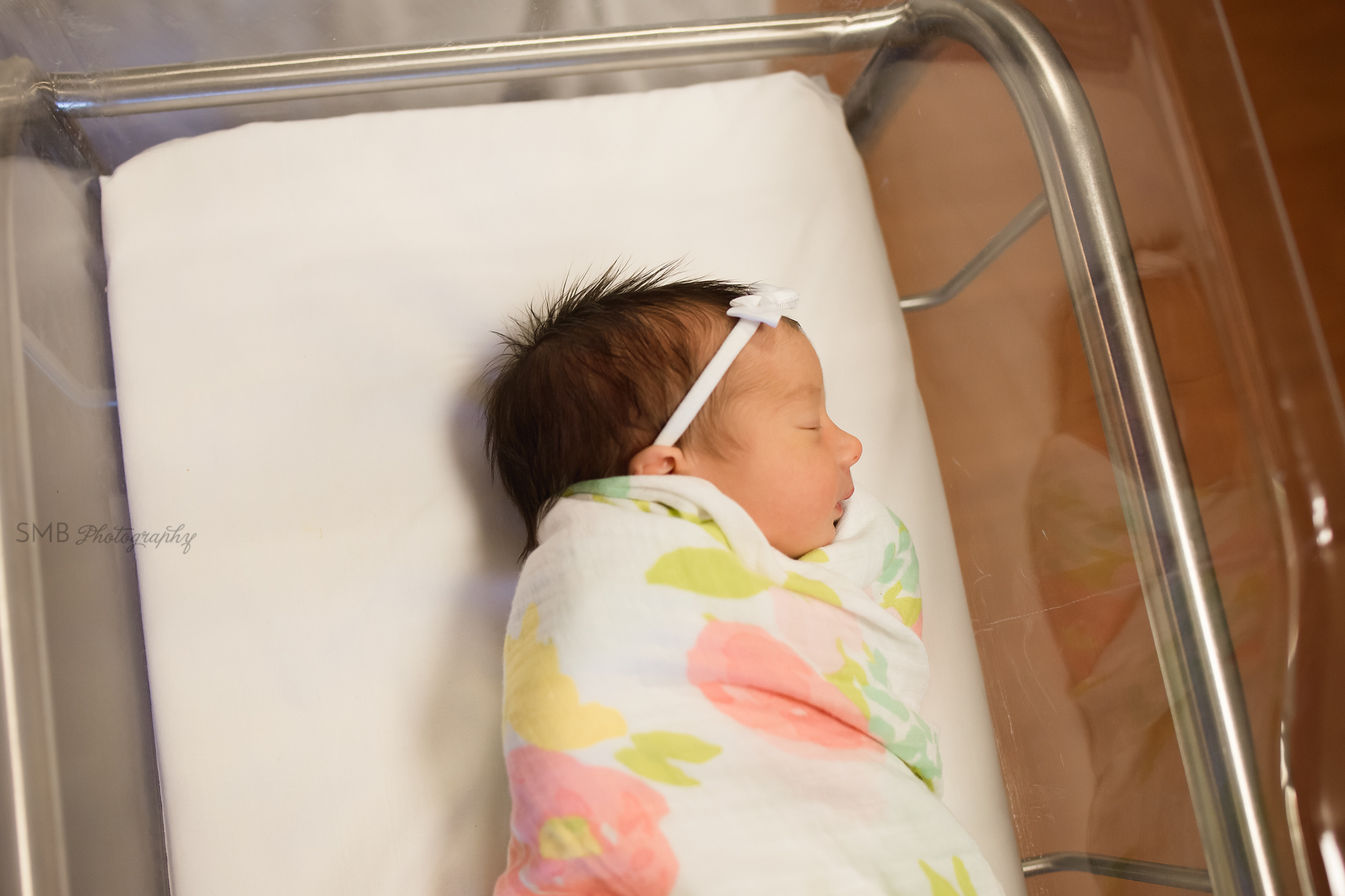 Baby girl wrapped in hospital bassinet
