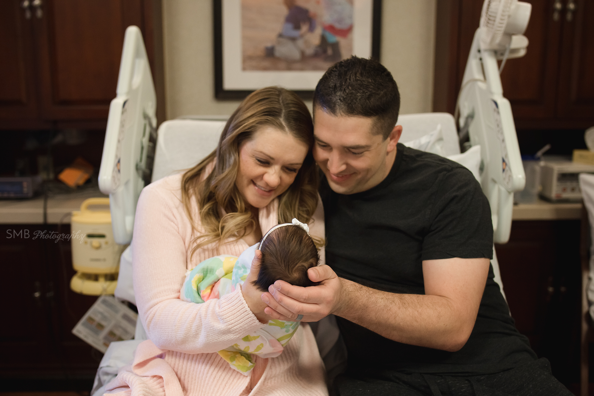 Mom and Dad holding newborn daughter in hospital