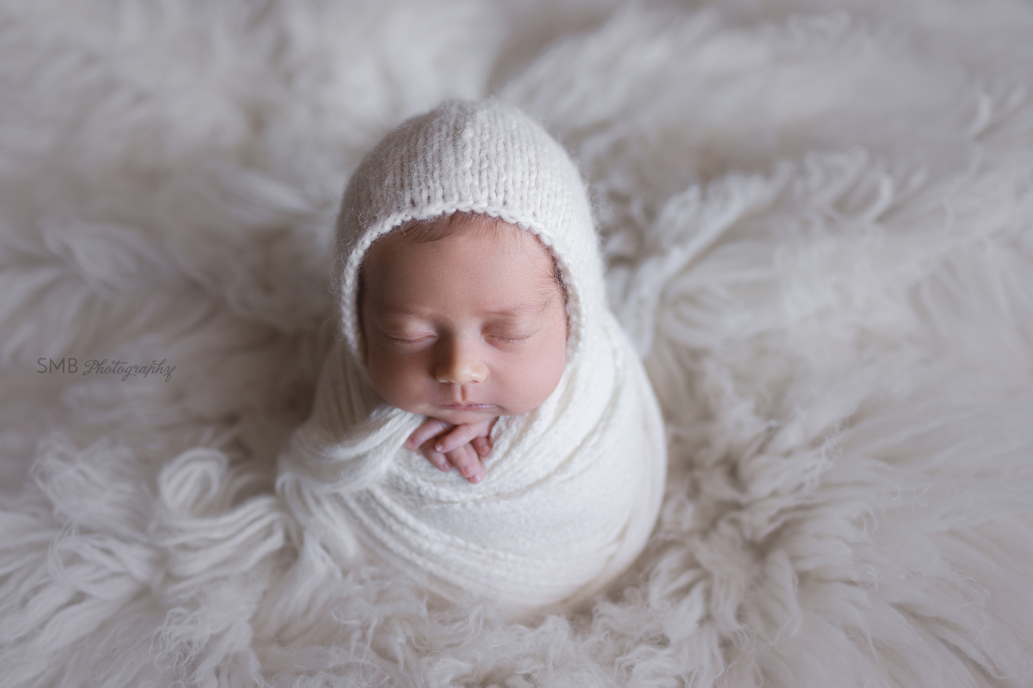 Newborn girl on white flokati wrapped