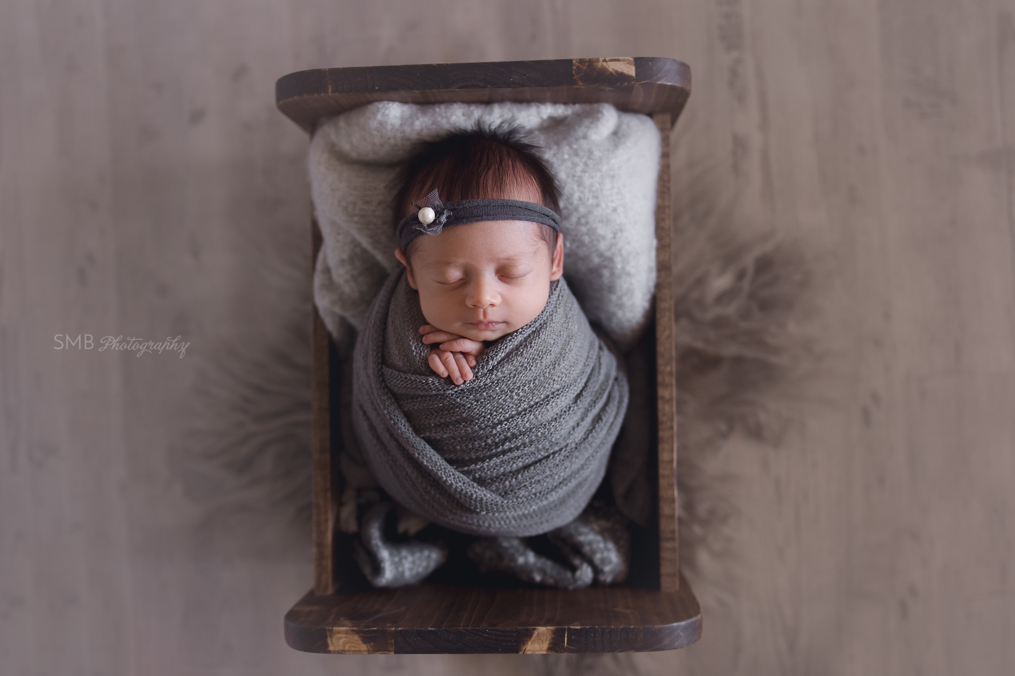 Newborn girl wrapped in baby cradle