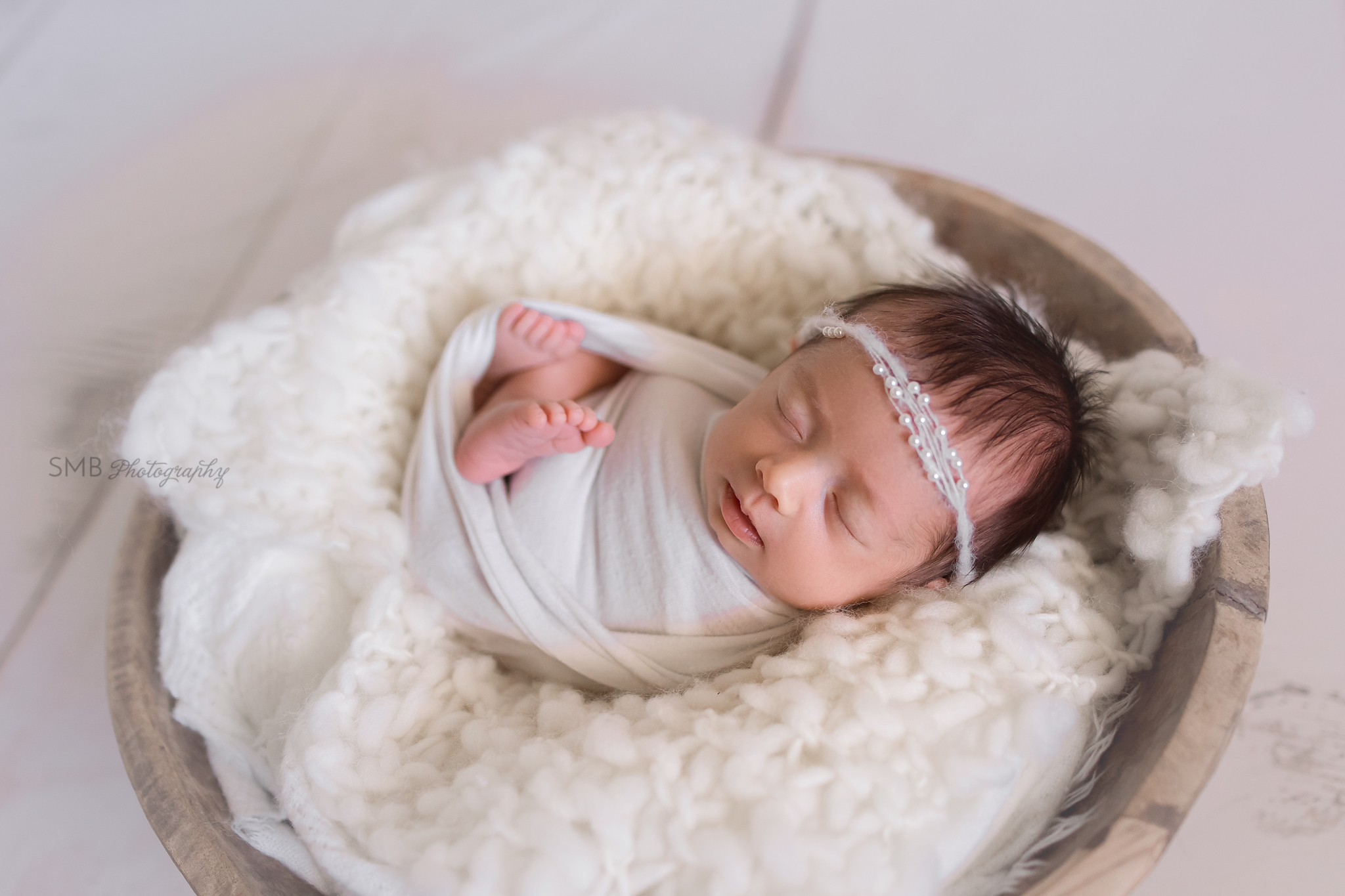 Newborn girl in wooden bowl