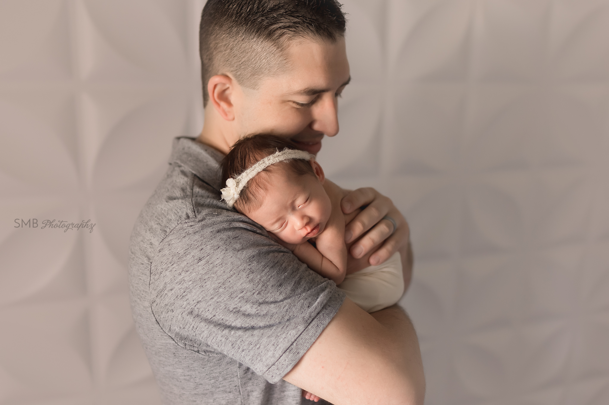Dad holding newborn daughter