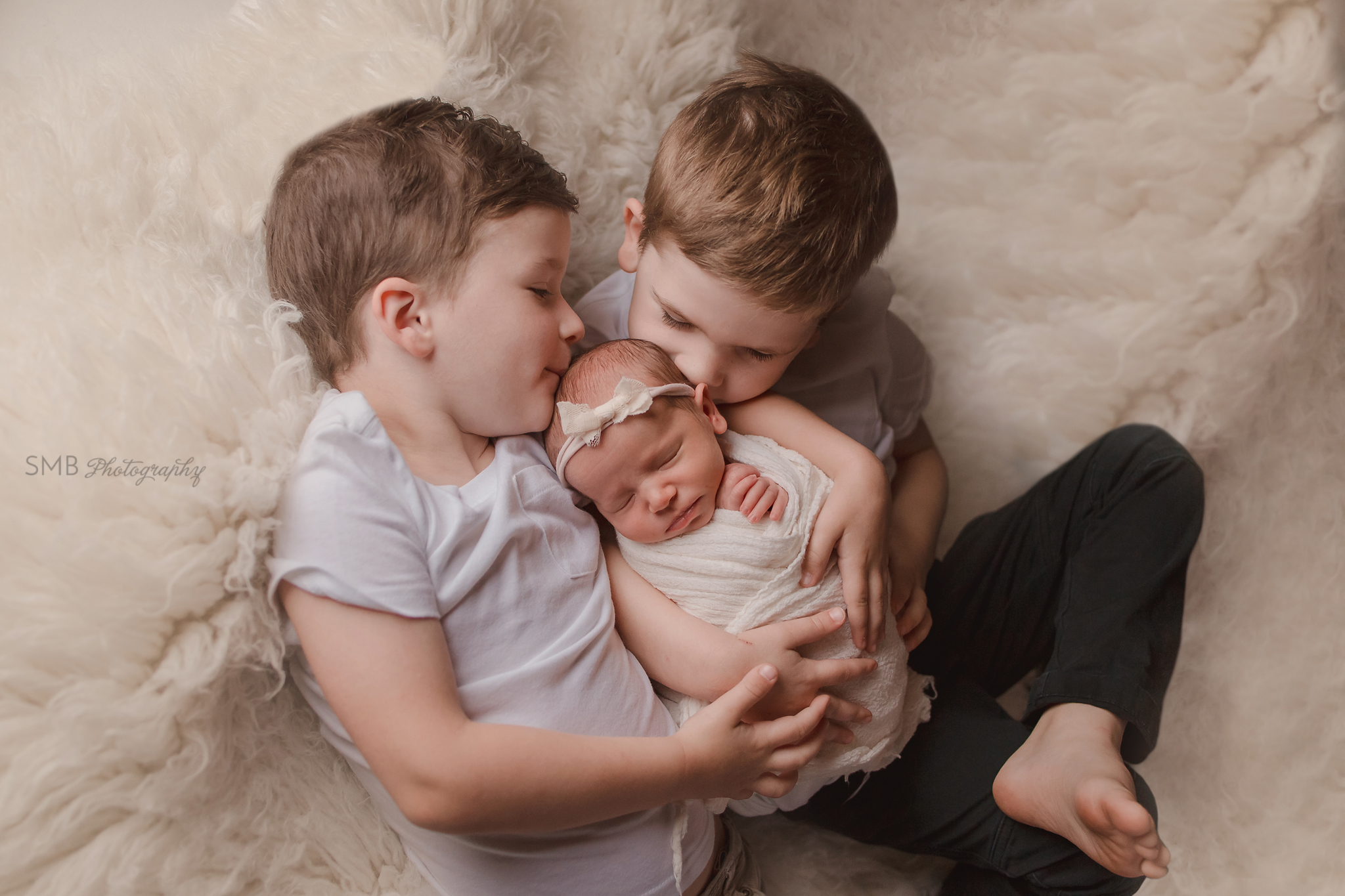 Big brothers kissing baby sister on white flokati