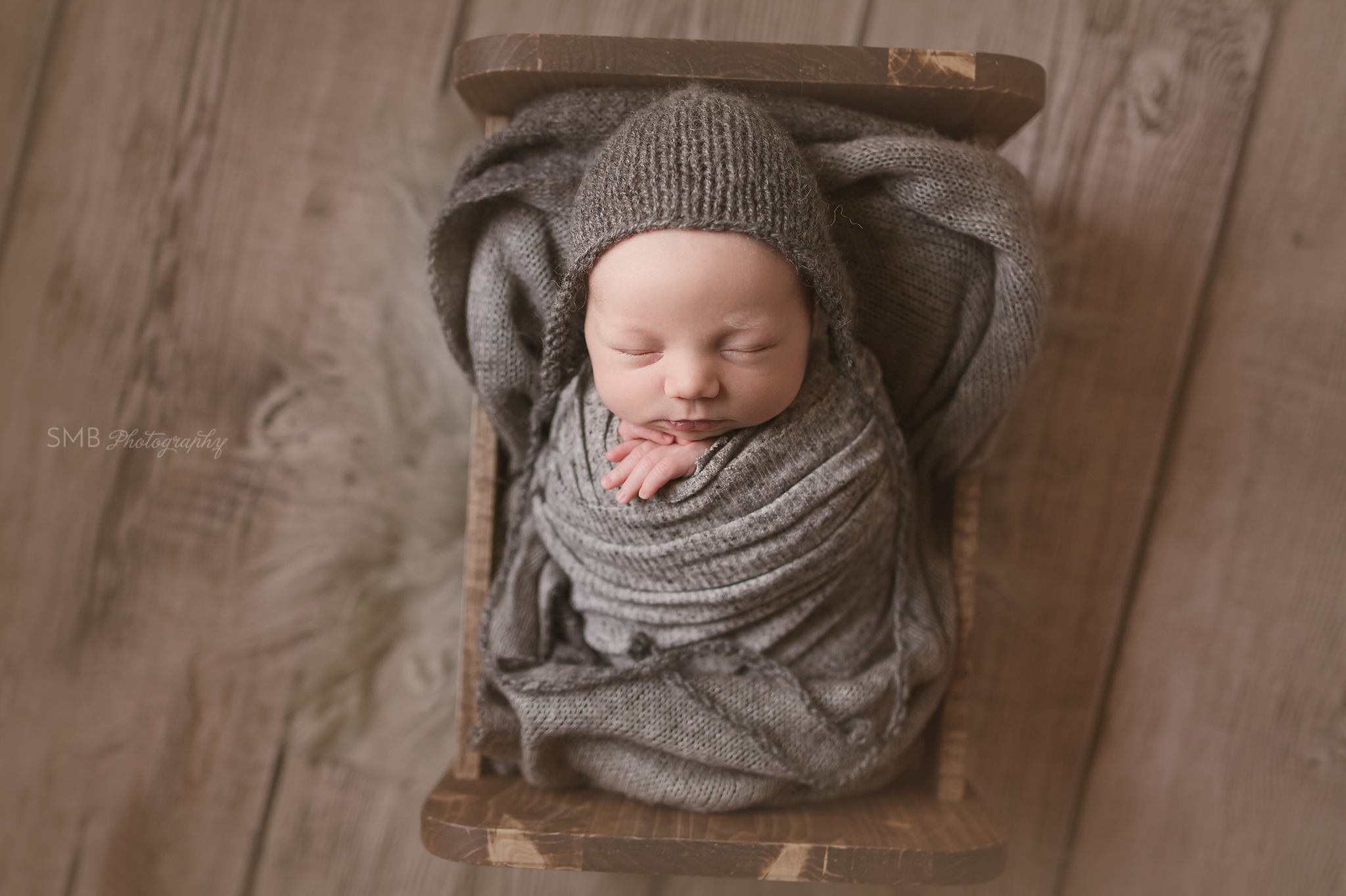 Newborn boy wrapped in baby bed