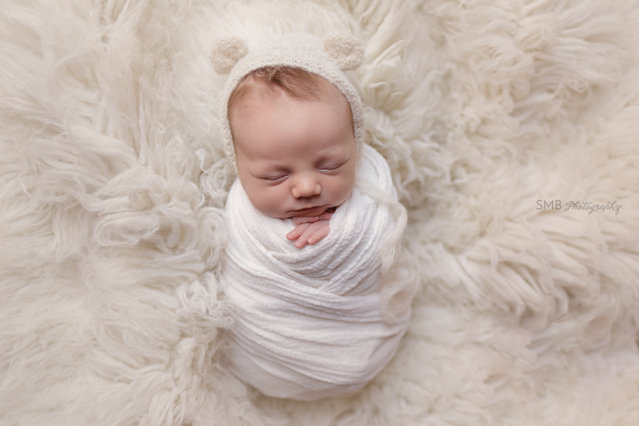 Baby boy wrapped on cream fur rug
