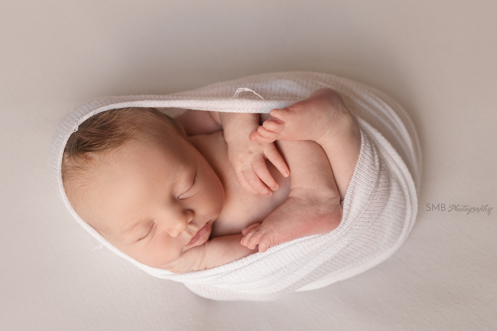 Baby boy wrapped on ivory backdrop