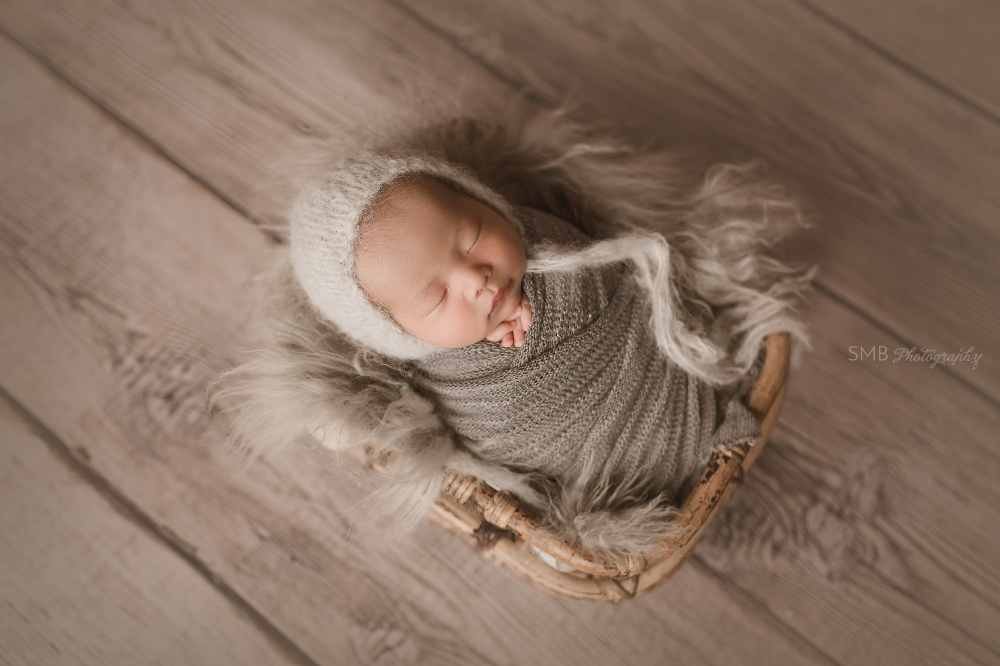 Baby boy wrapped in charcoal gray in bamboo basket