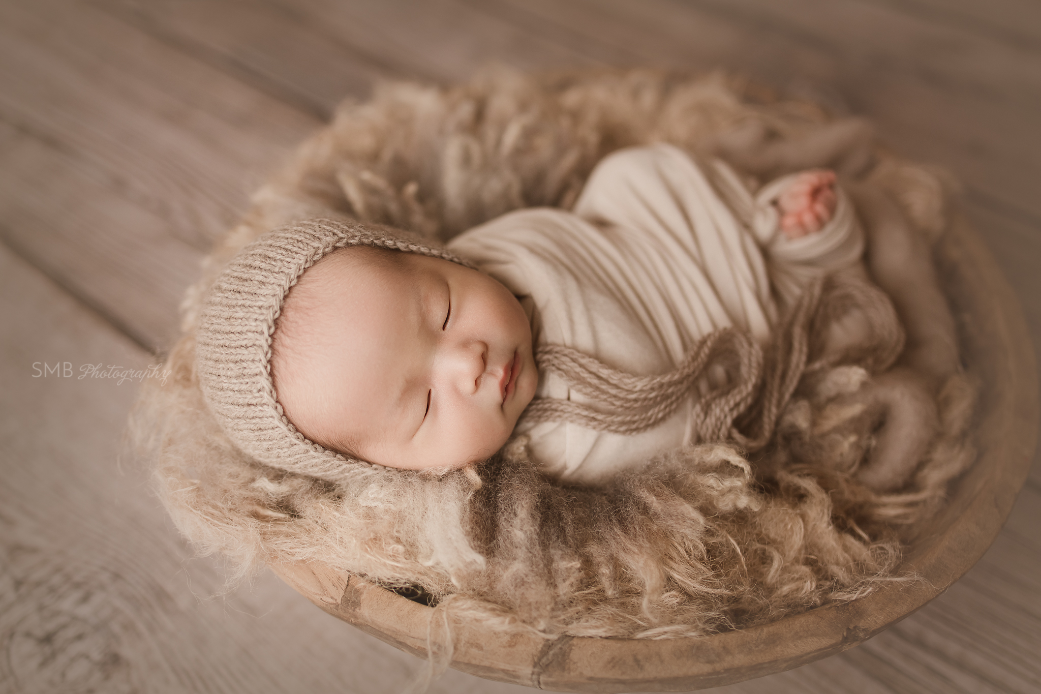 Newborn sleeping in large wood bowl