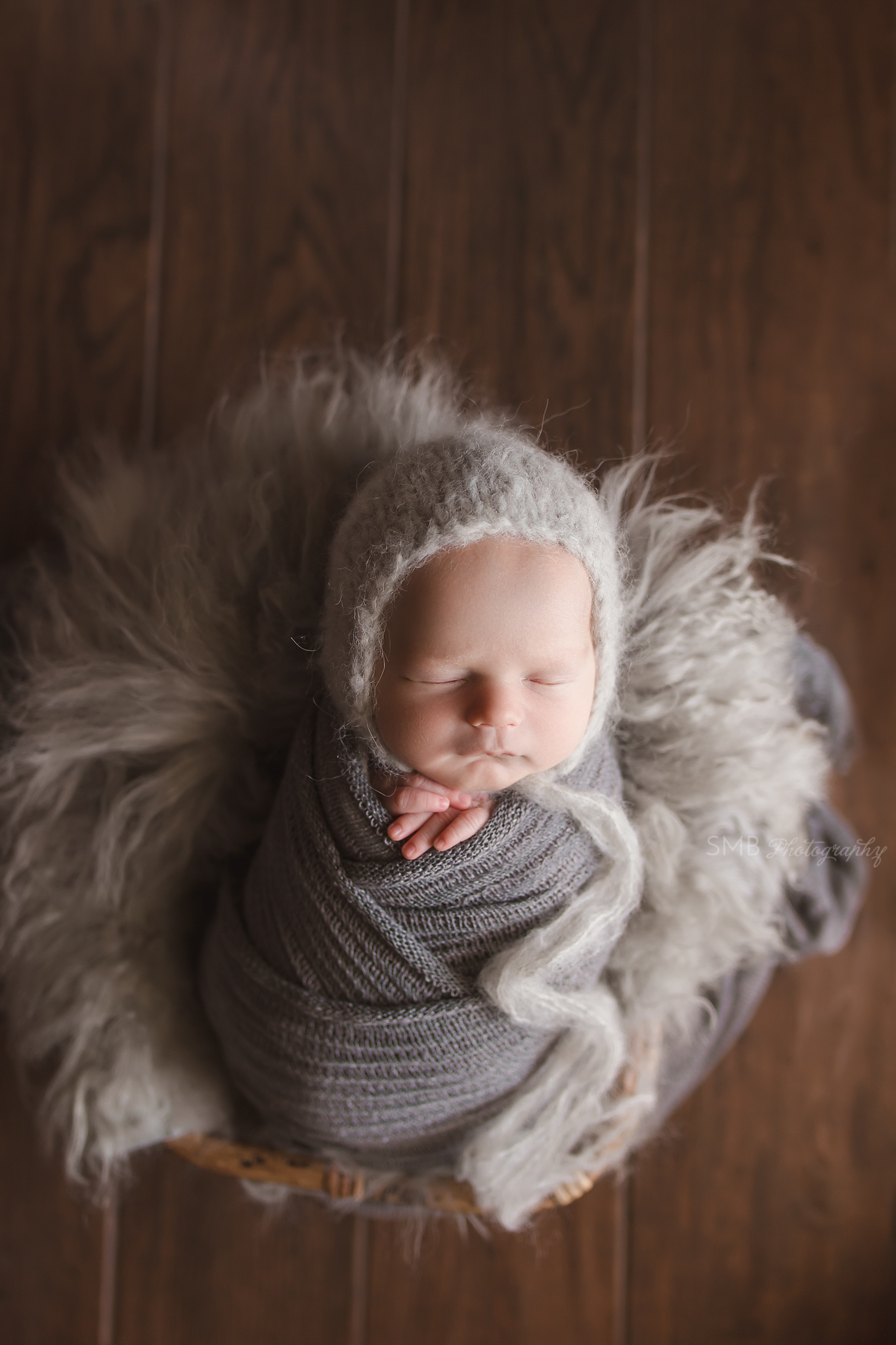 Baby boy wrapped in gray in bamboo basket