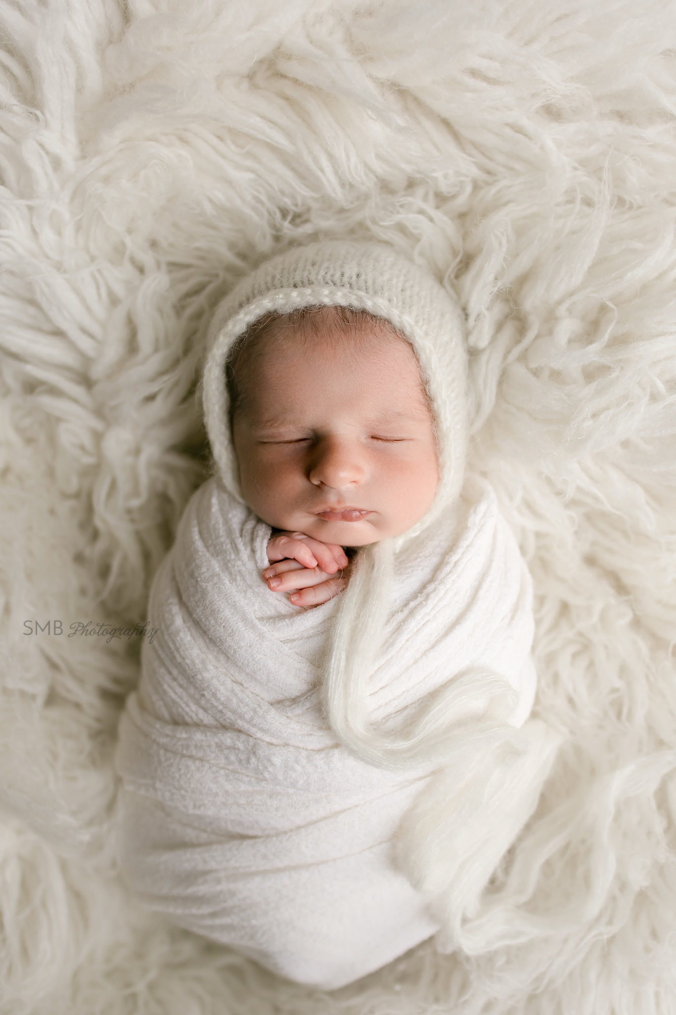 Newborn baby wrapped on white flokati