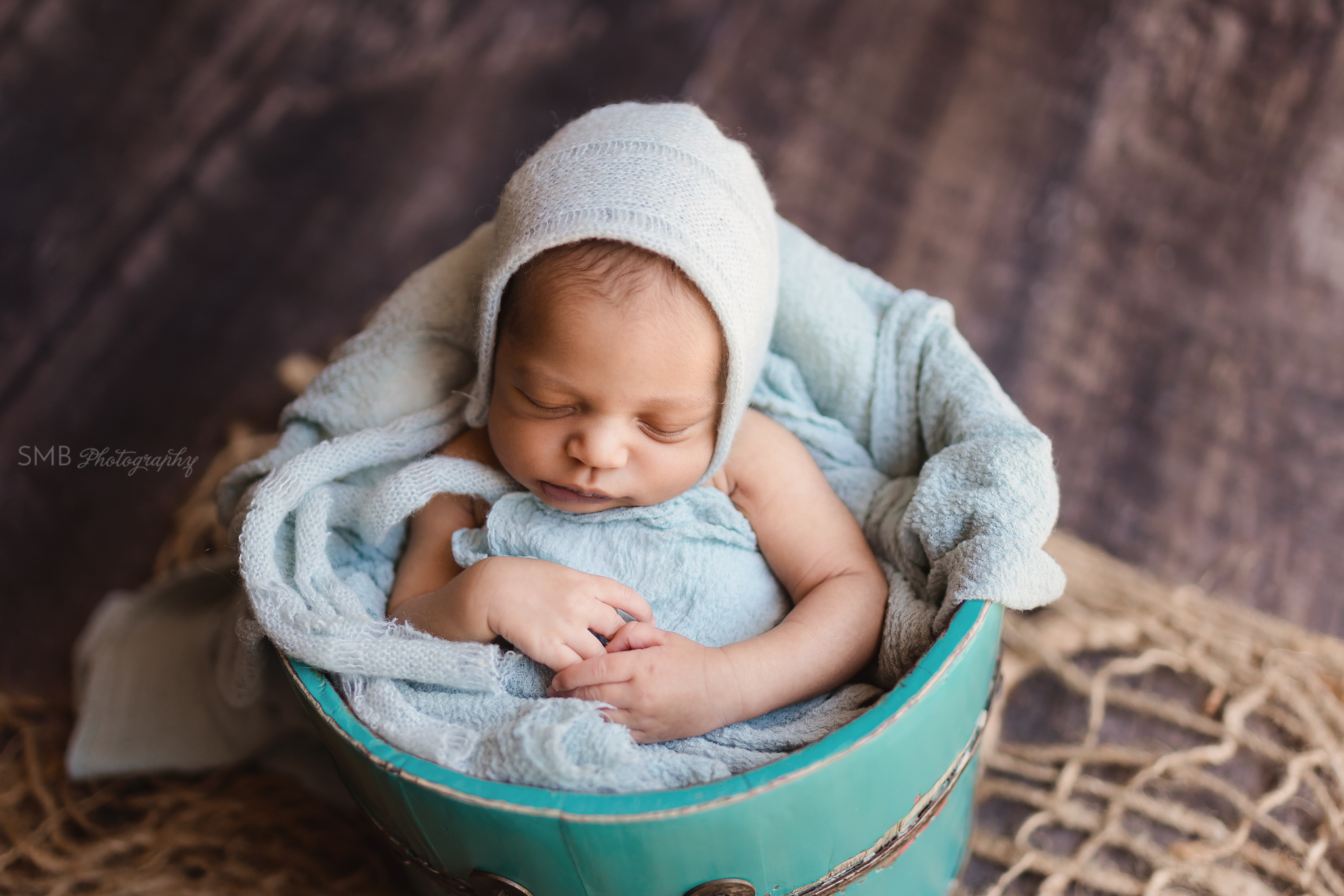 Baby boy sleeping in teal bucket