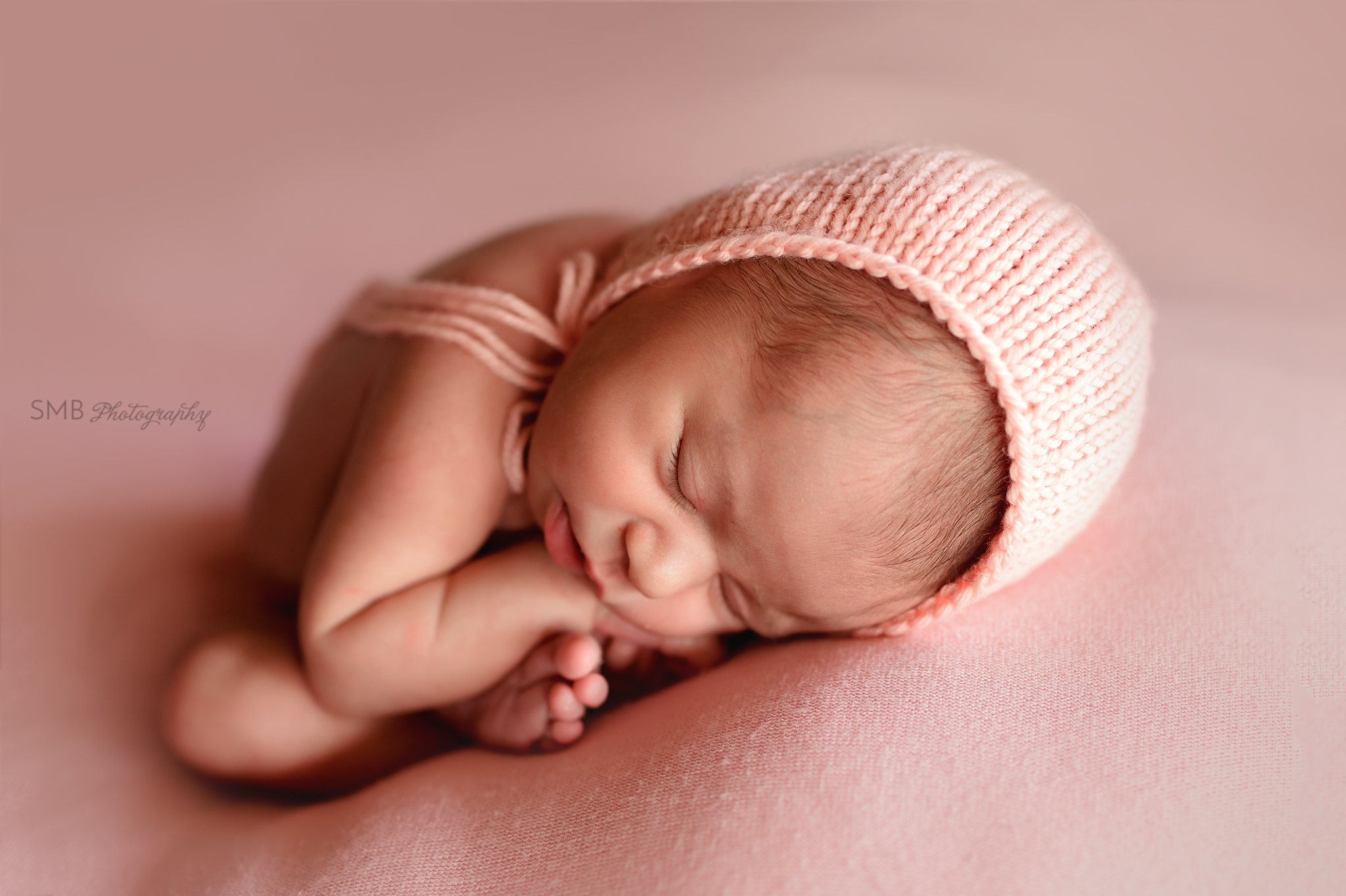 Newborn curled in womb like pose