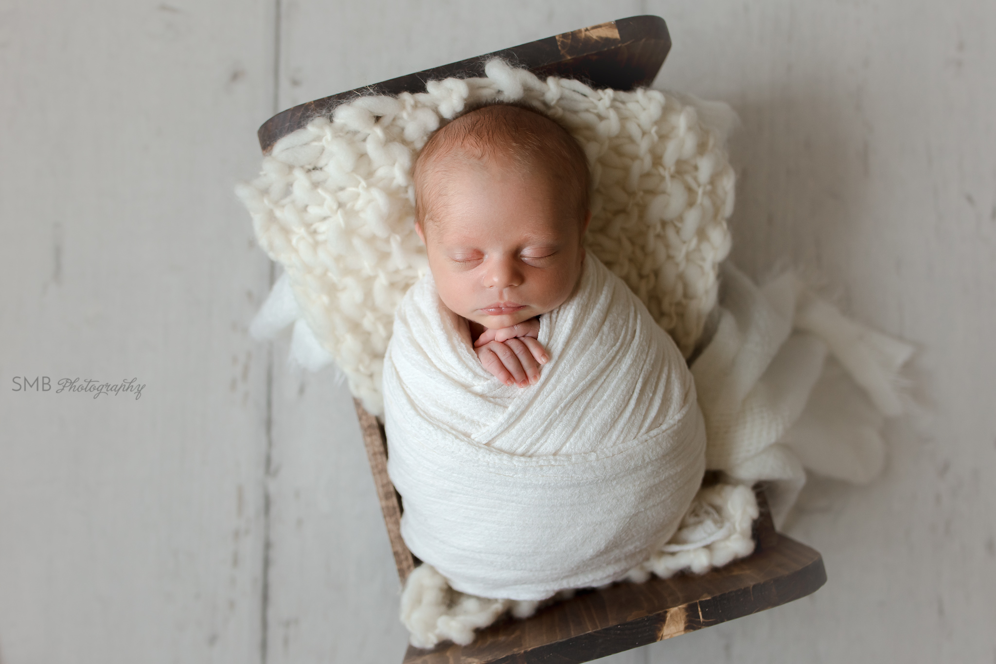 Baby boy wrapped in newborn cradle