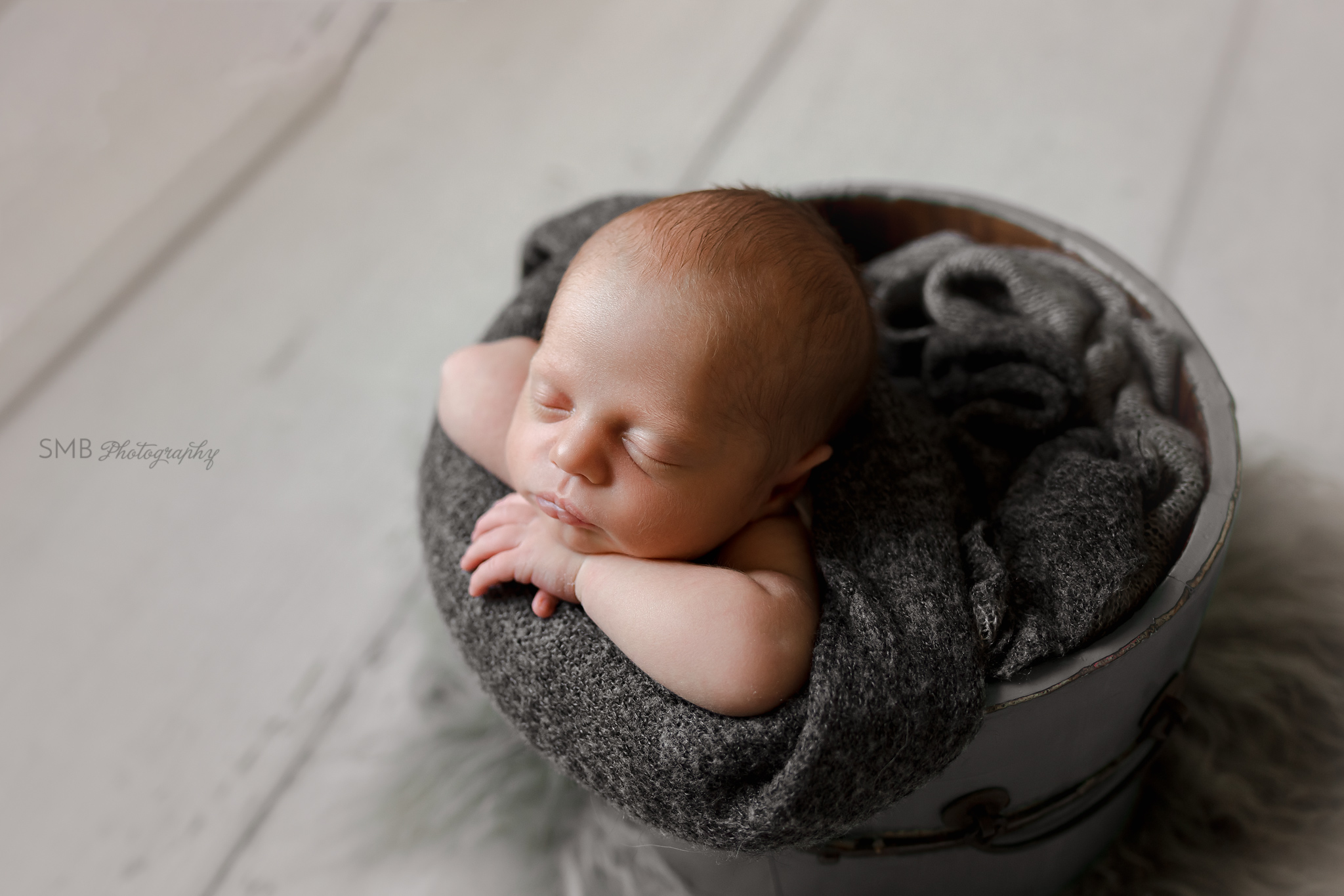 Profile portrait of new baby boy in bucket