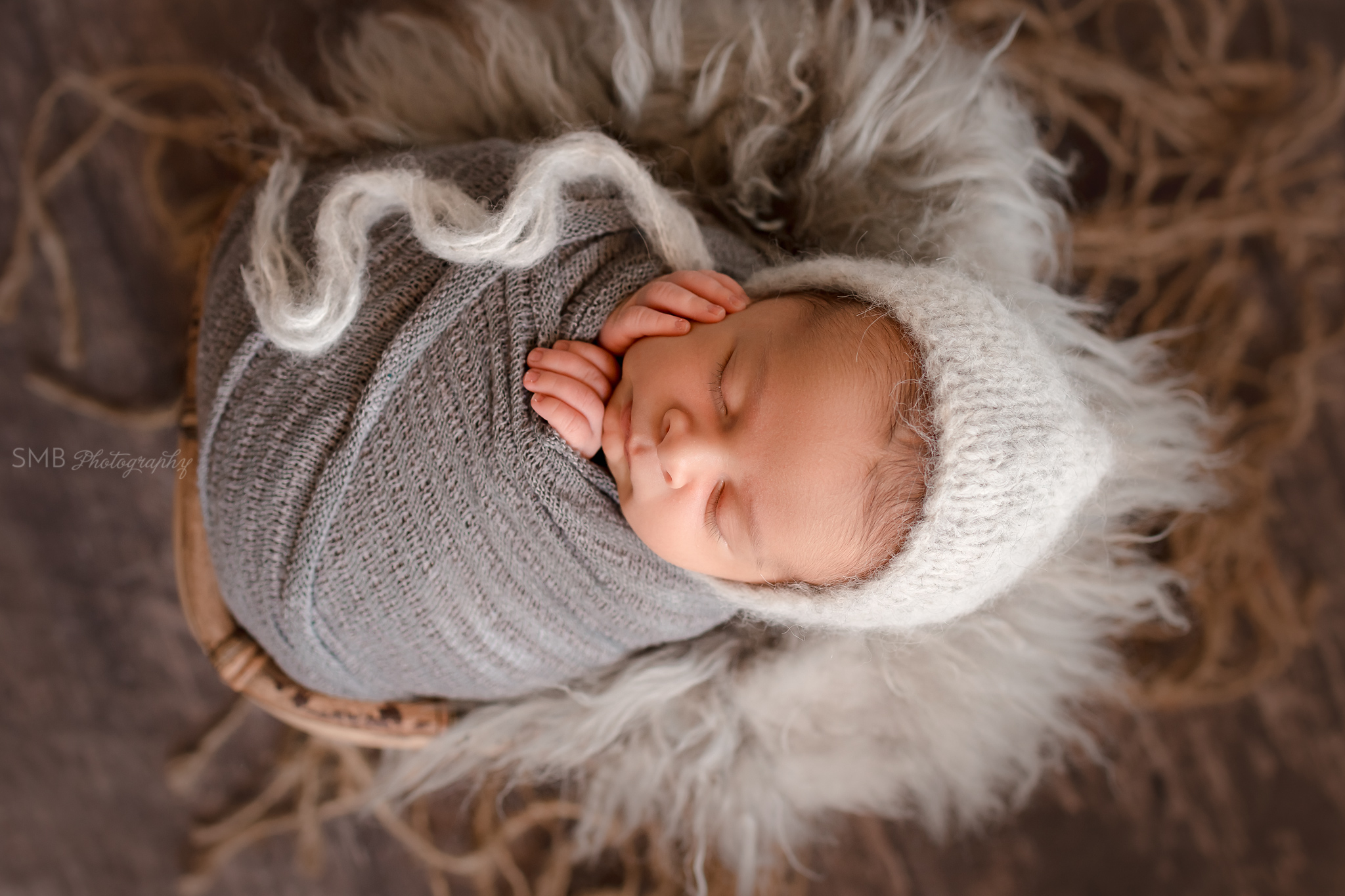 Baby boy wrapped in gray textured wrap, sleeping in bamboo basket