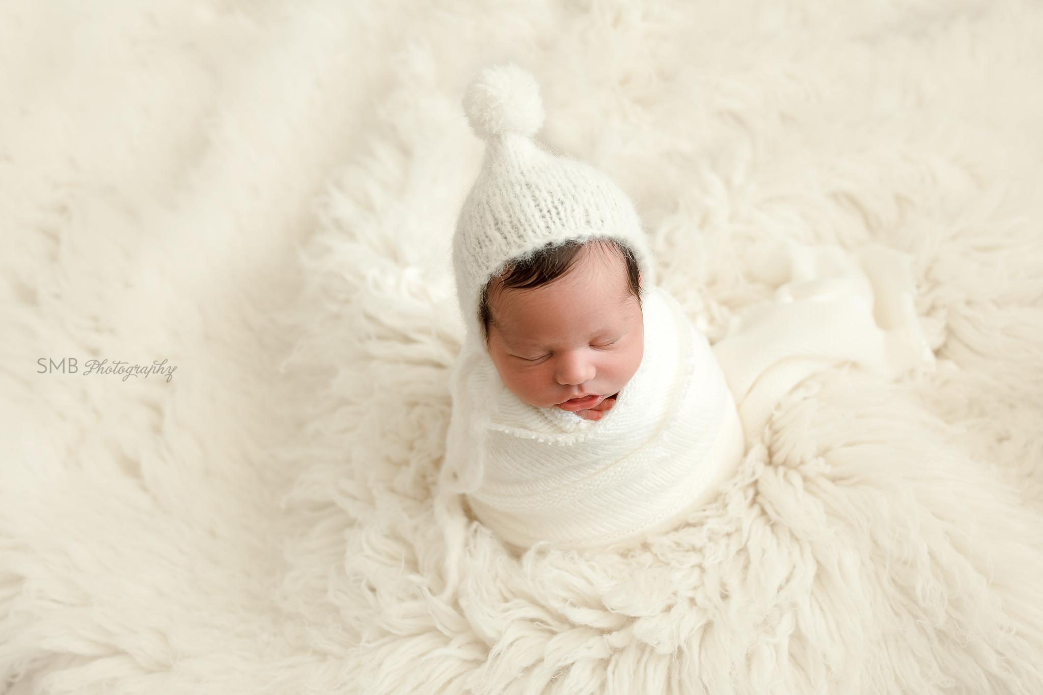 Baby wrapped in potato sack pose on white flokati