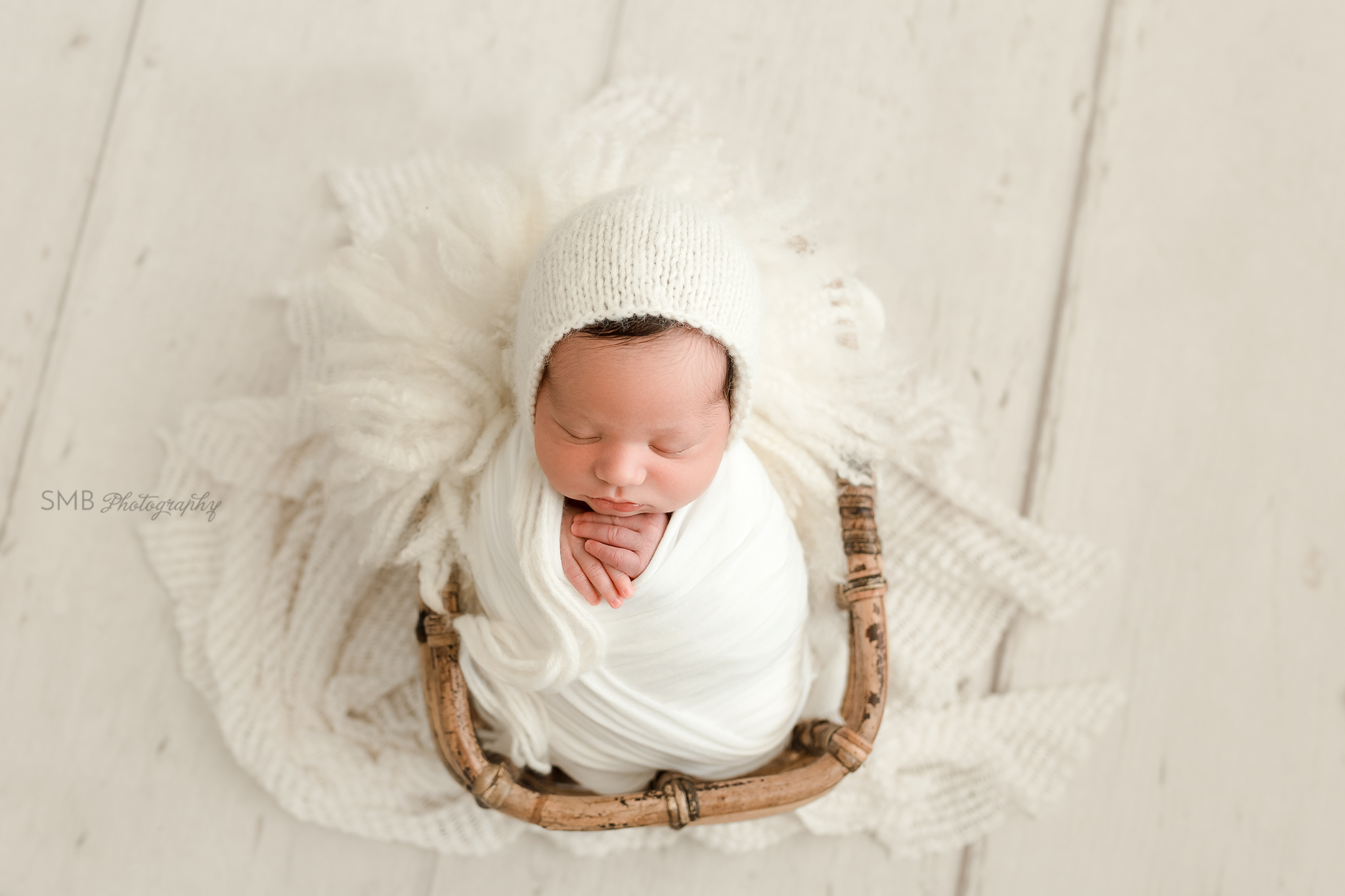 Newborn wrapped in white in bamboo basket