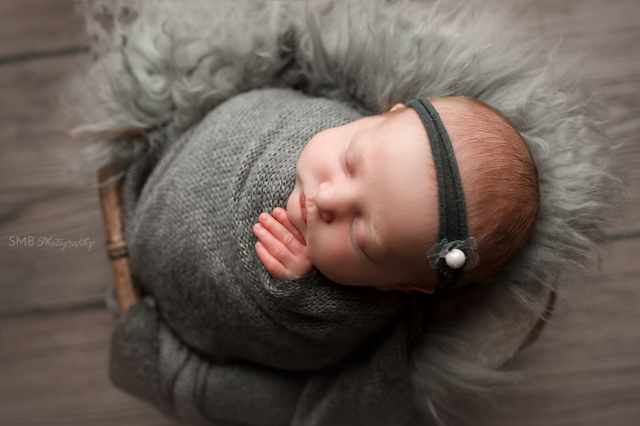 Newborn baby girl wrapped in dark gray in bamboo basket