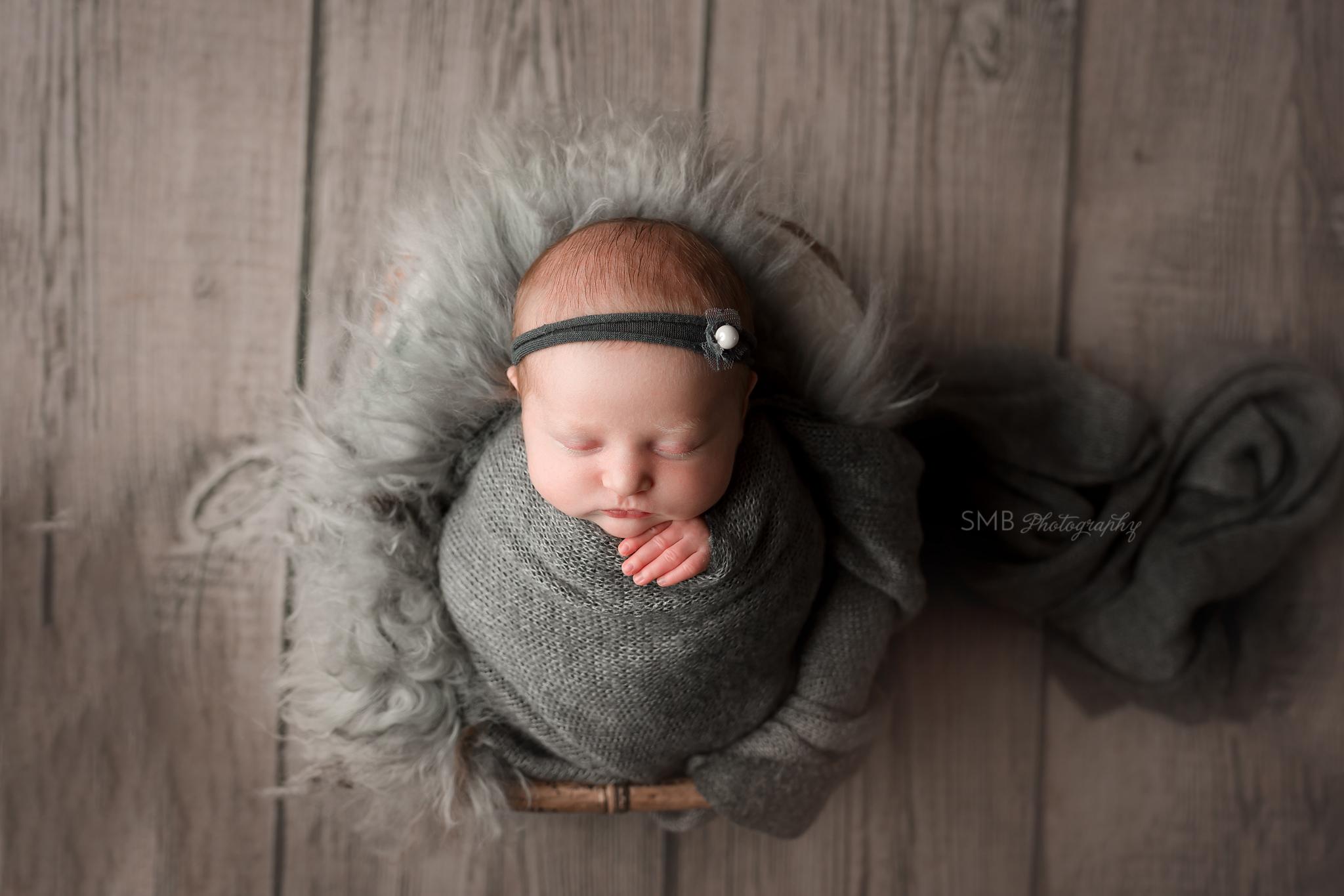 Newborn baby in basket with gray fur