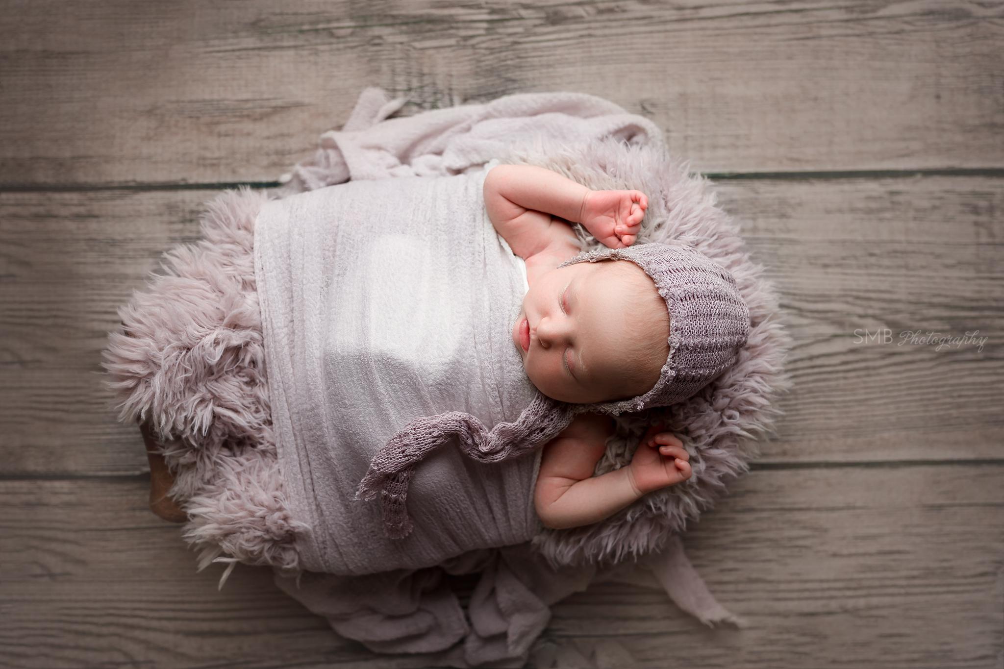 Newborn girl wearing purple fringe bonnet