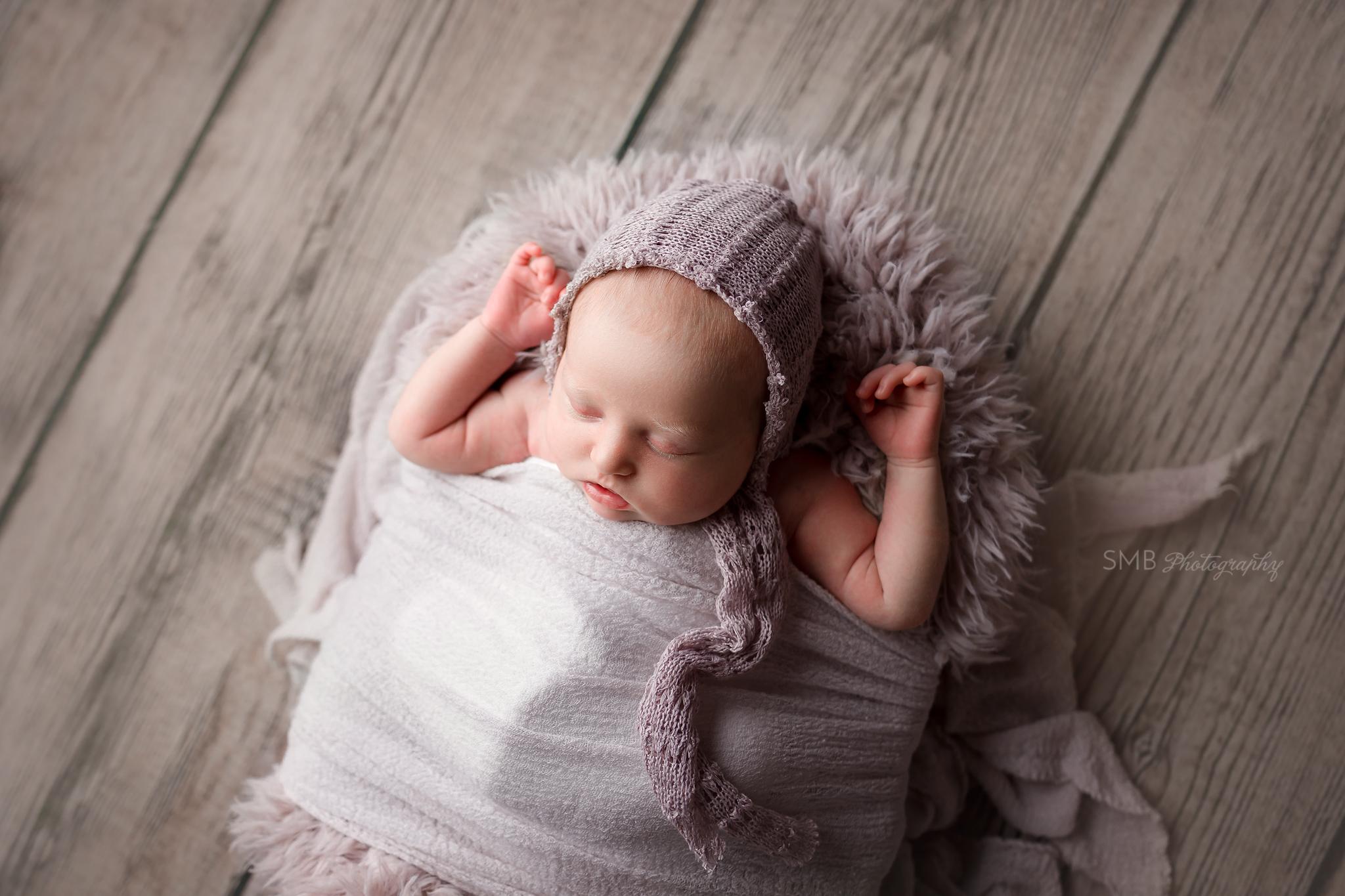 Newborn girl sleeping on purple fur