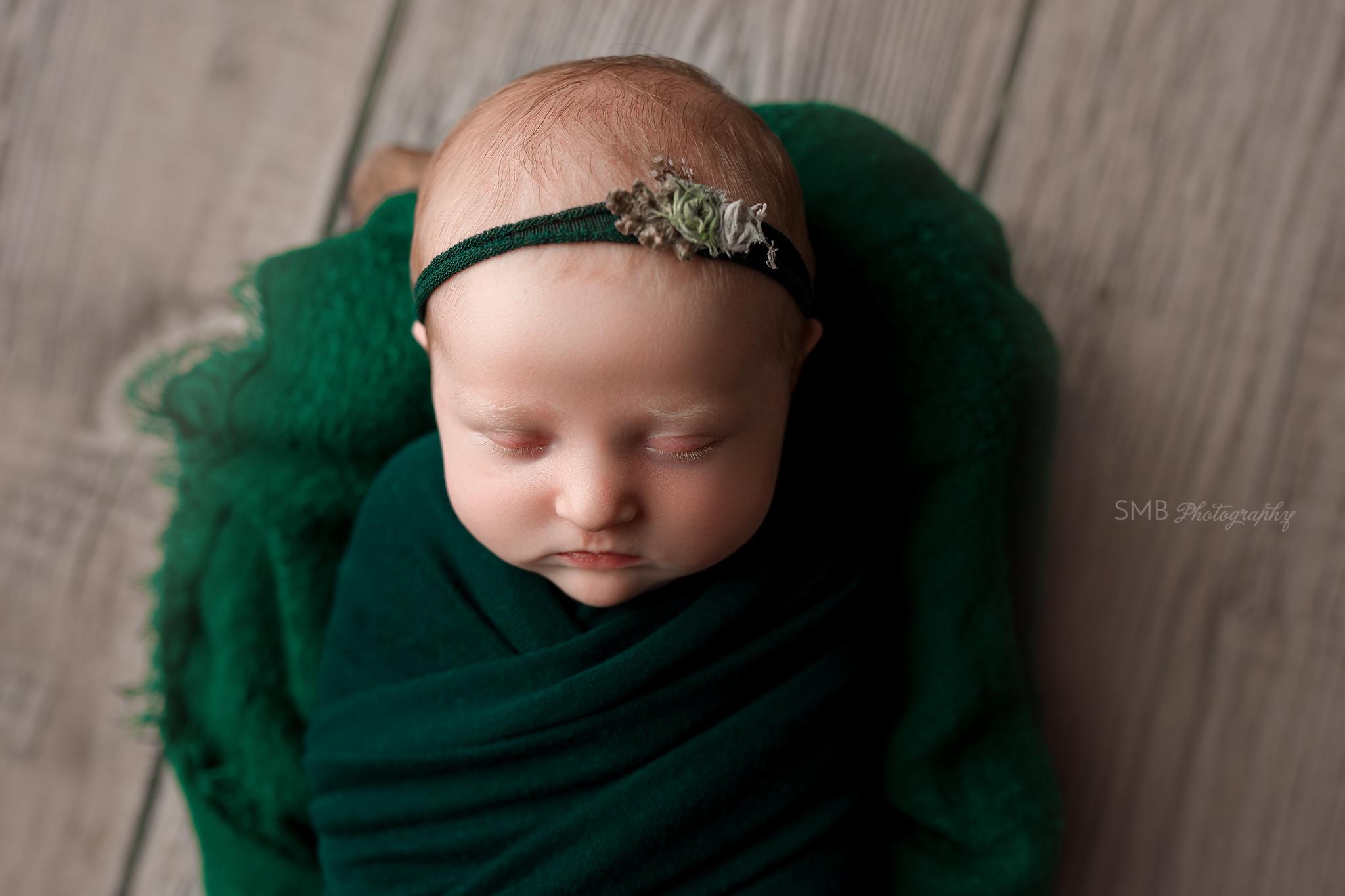 Newborn girl wrapped in hunter green