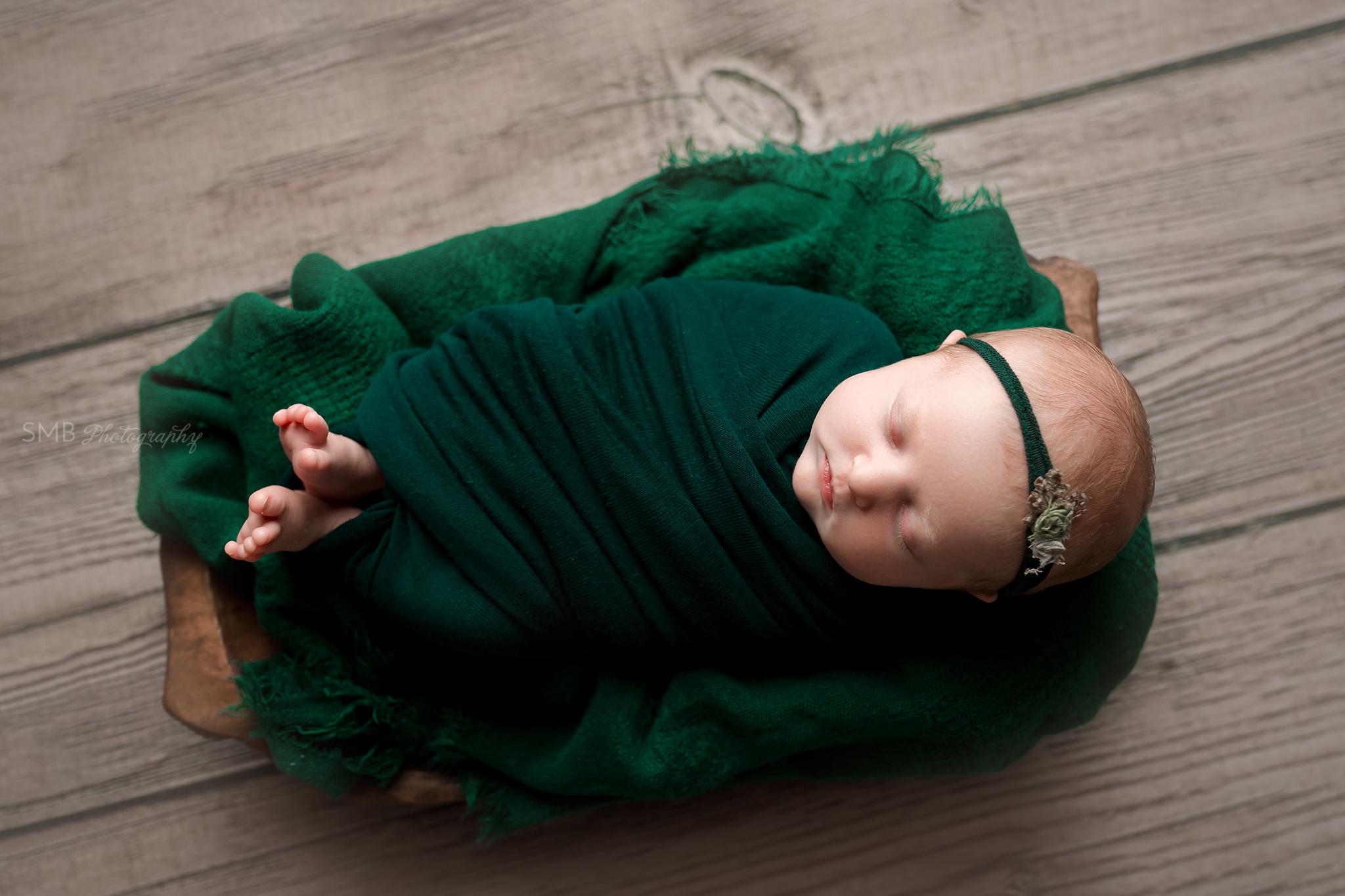 Newborn sleeping in wood trencher