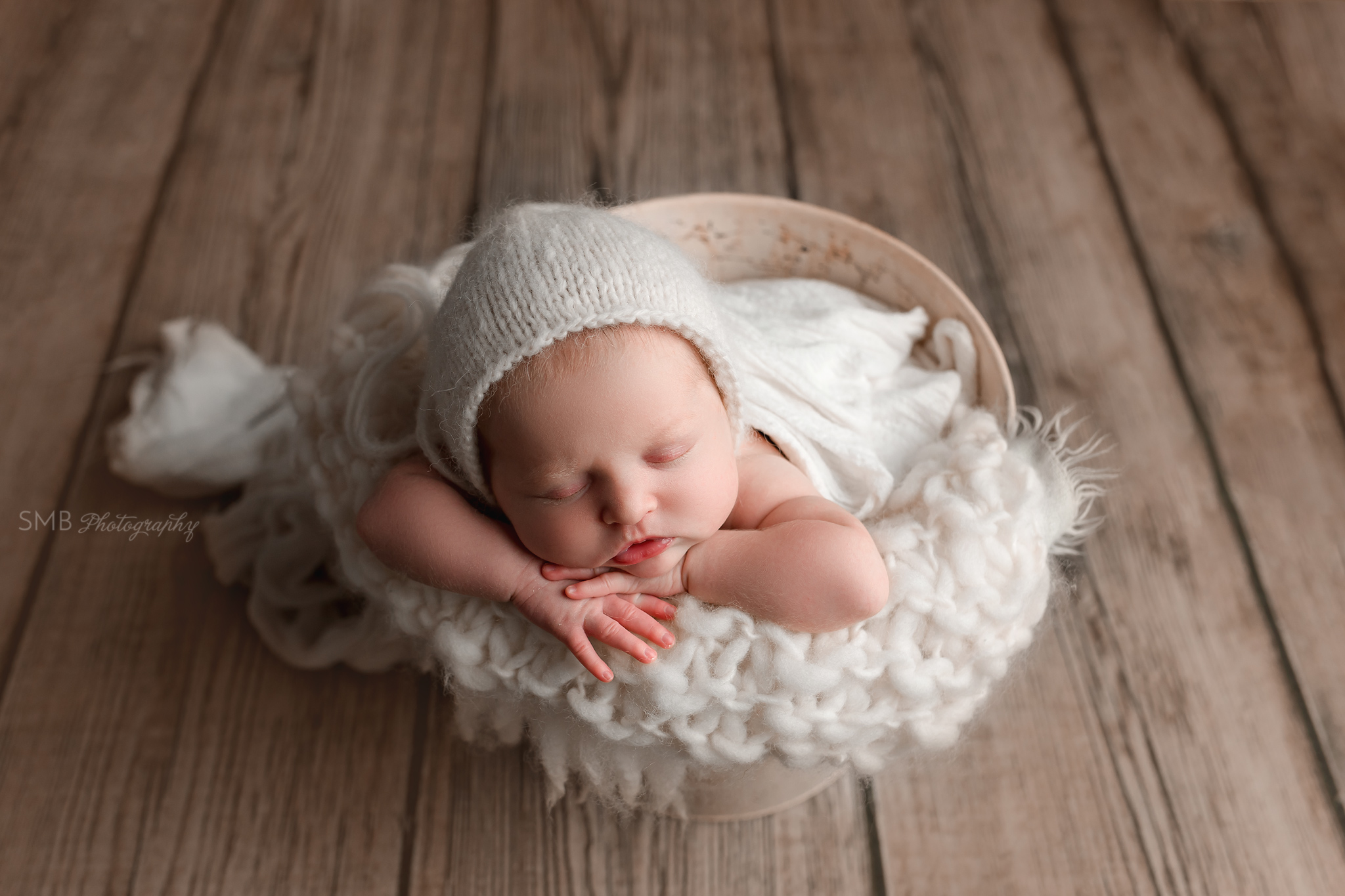 Newborn baby in cream bucket