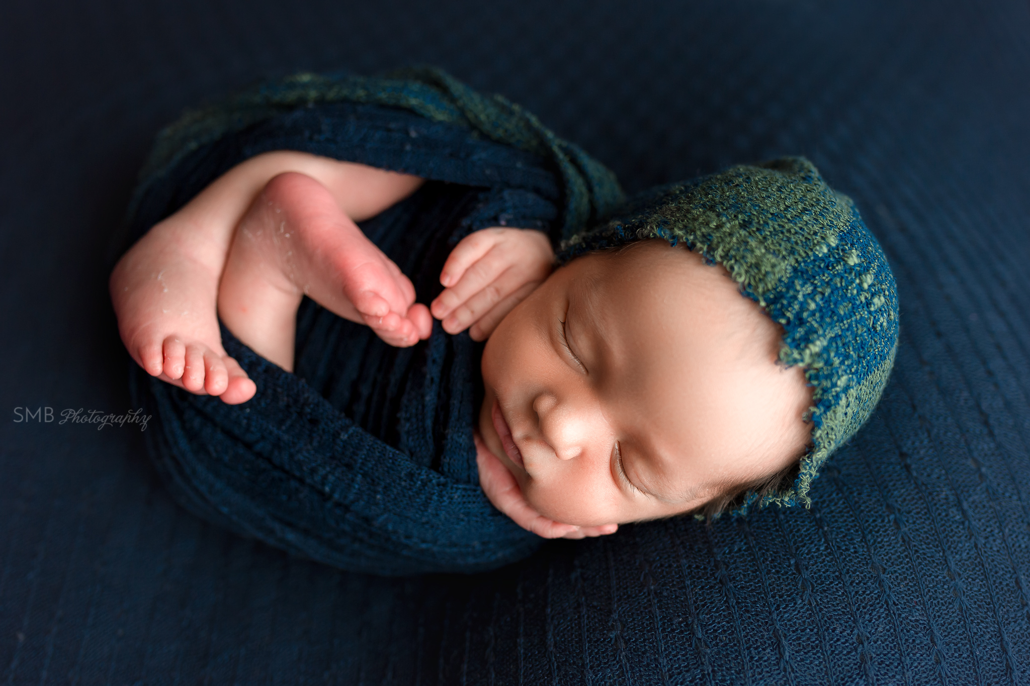Newborn boy holding cheek wrapped on navy backdrop