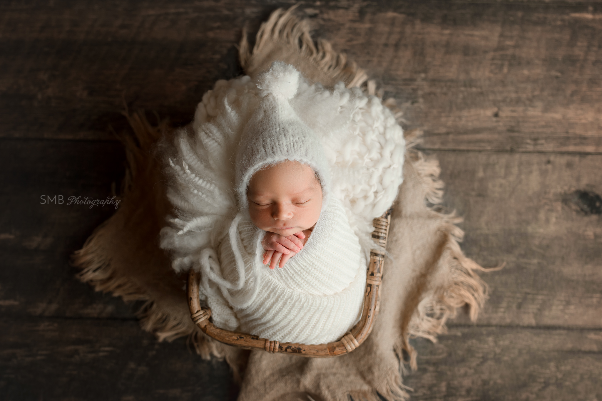 Newborn wearing pom pom bonnet