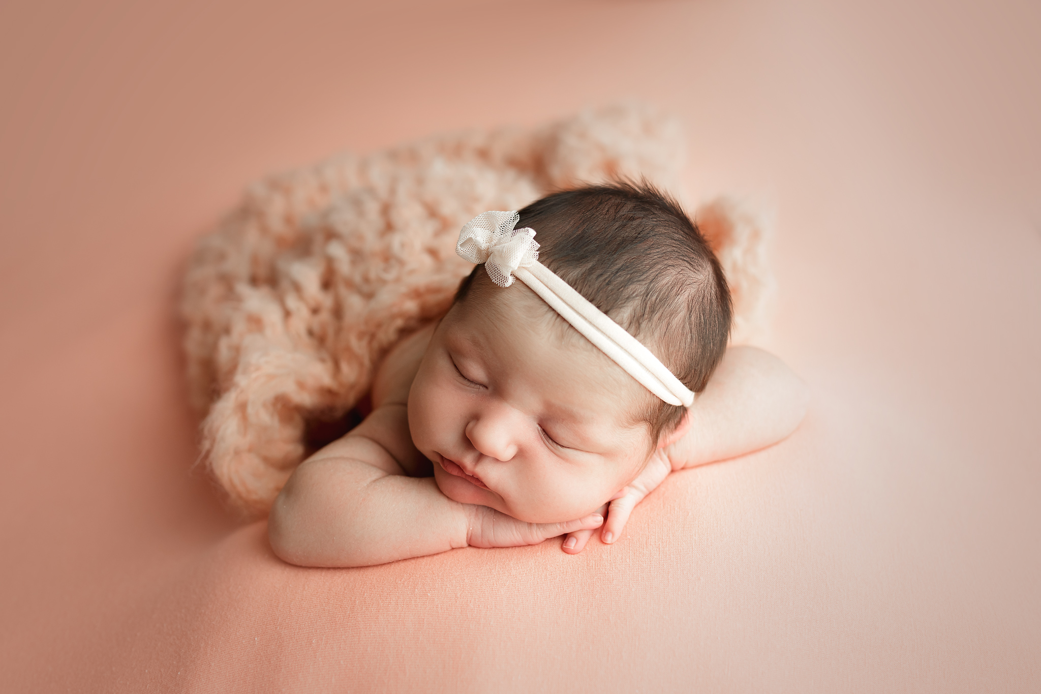 Newborn girl on purple blanket with purple headband