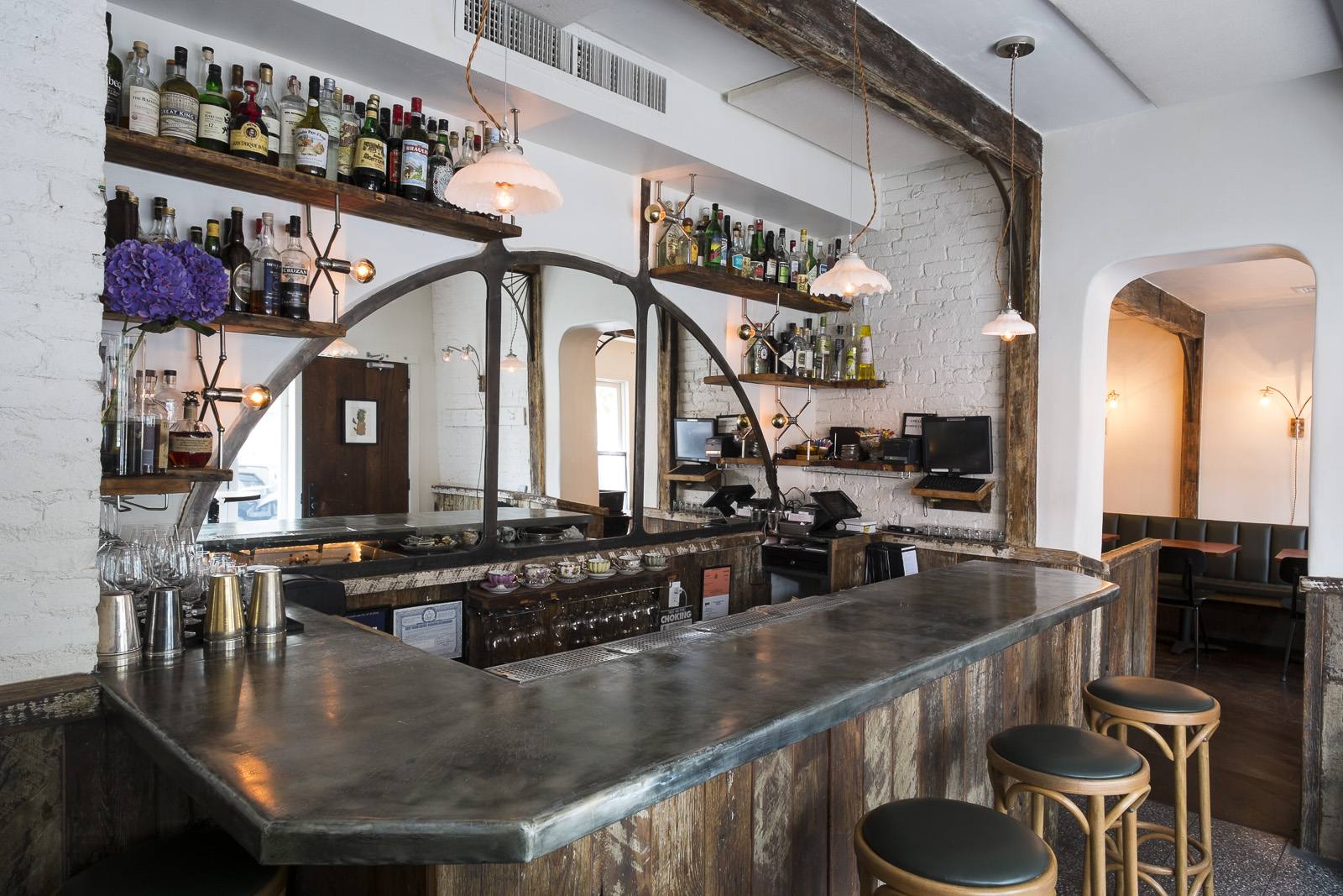 back bar with custom mirror and ironwork, custom integrated lighting, custom bar lighting with repurposed antique shades