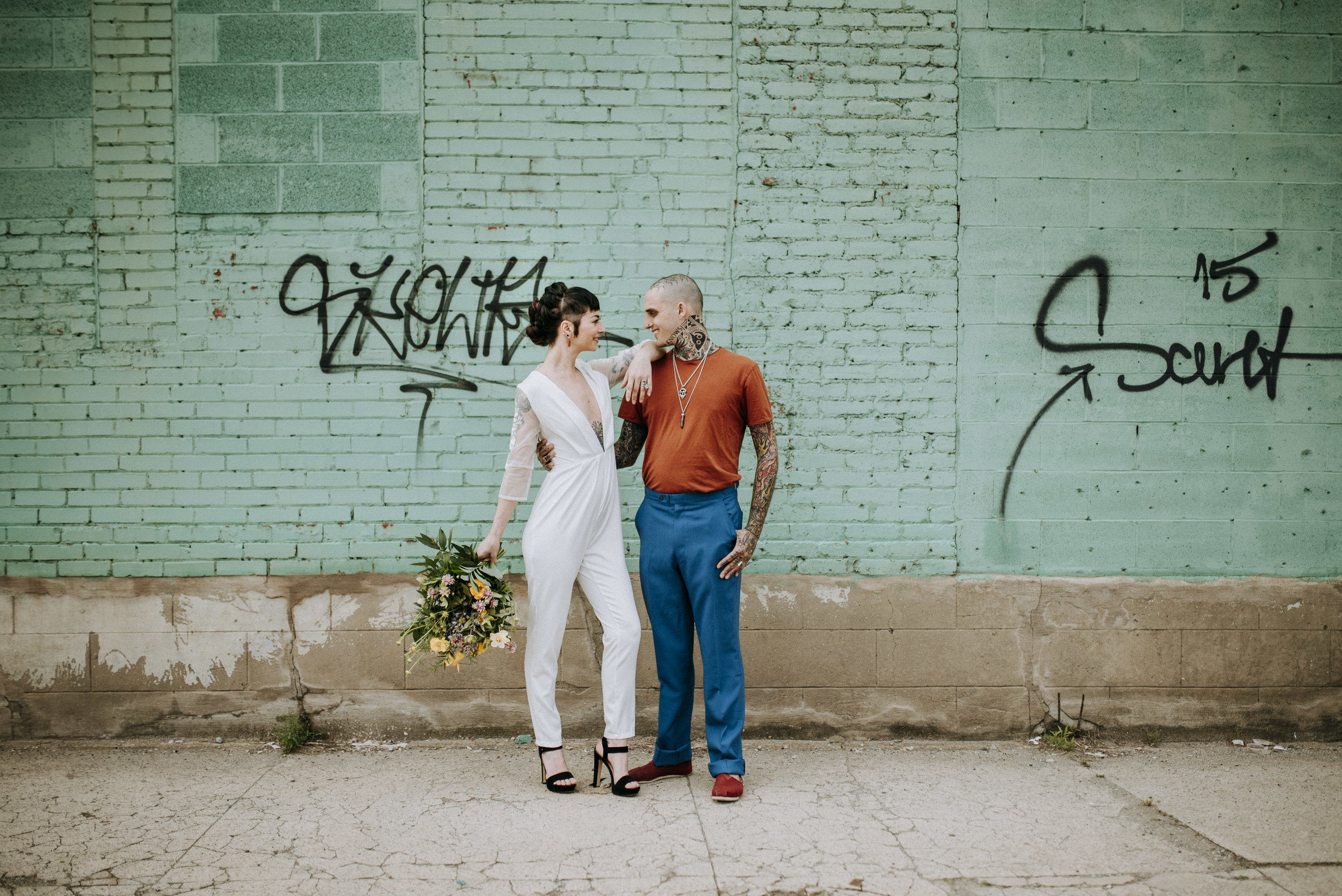 A $10 white vintage jumpsuit for the bride, shoes that she already owned, $20 thrifted pants for the groom, and the rest he already owned. $30 total | Photo by Sandrachile.