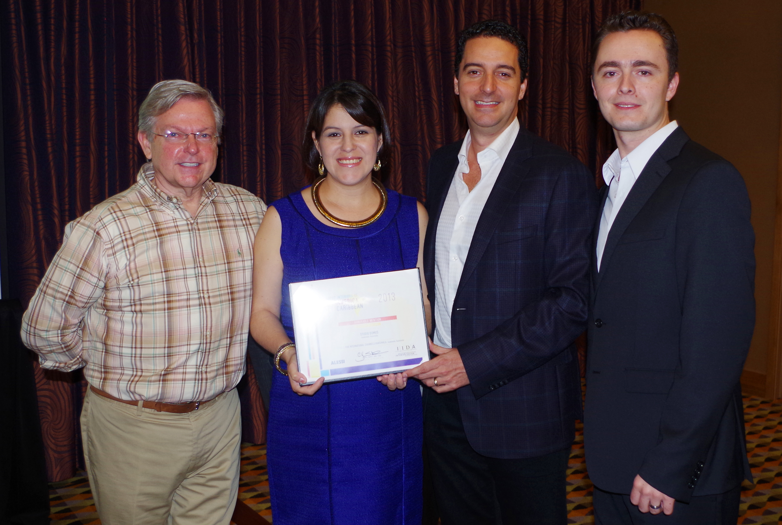Ana Lucia, Mauricio and Jose Pablo collect the certificate withDennis Krause Senior Vice President IIDA