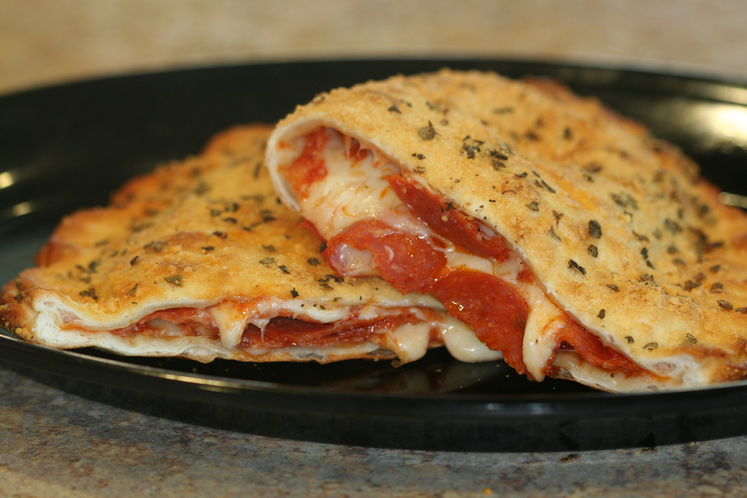 Calzones - Our freshly made pizza dough filled with pizza sauce, cheese & your choice of up to 3 toppings (please limit toppings to 3 or less)Only $7.99