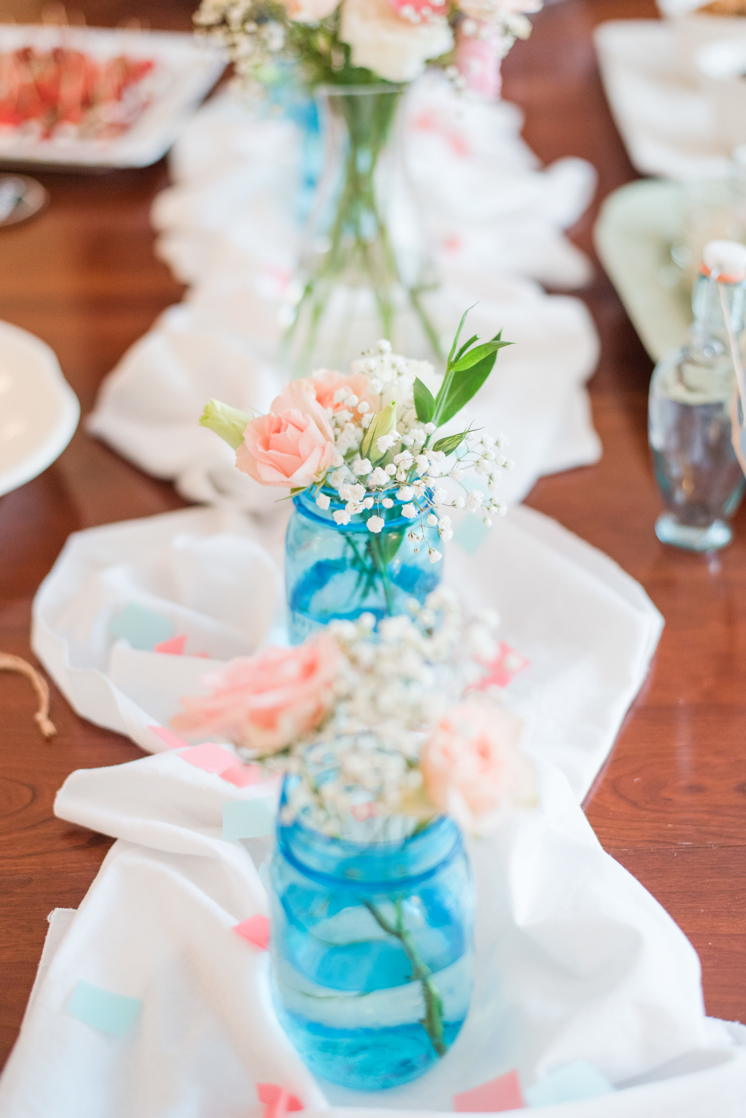 Pink flowers in blue mason jars [Photo: Courtney Timms Photography]
