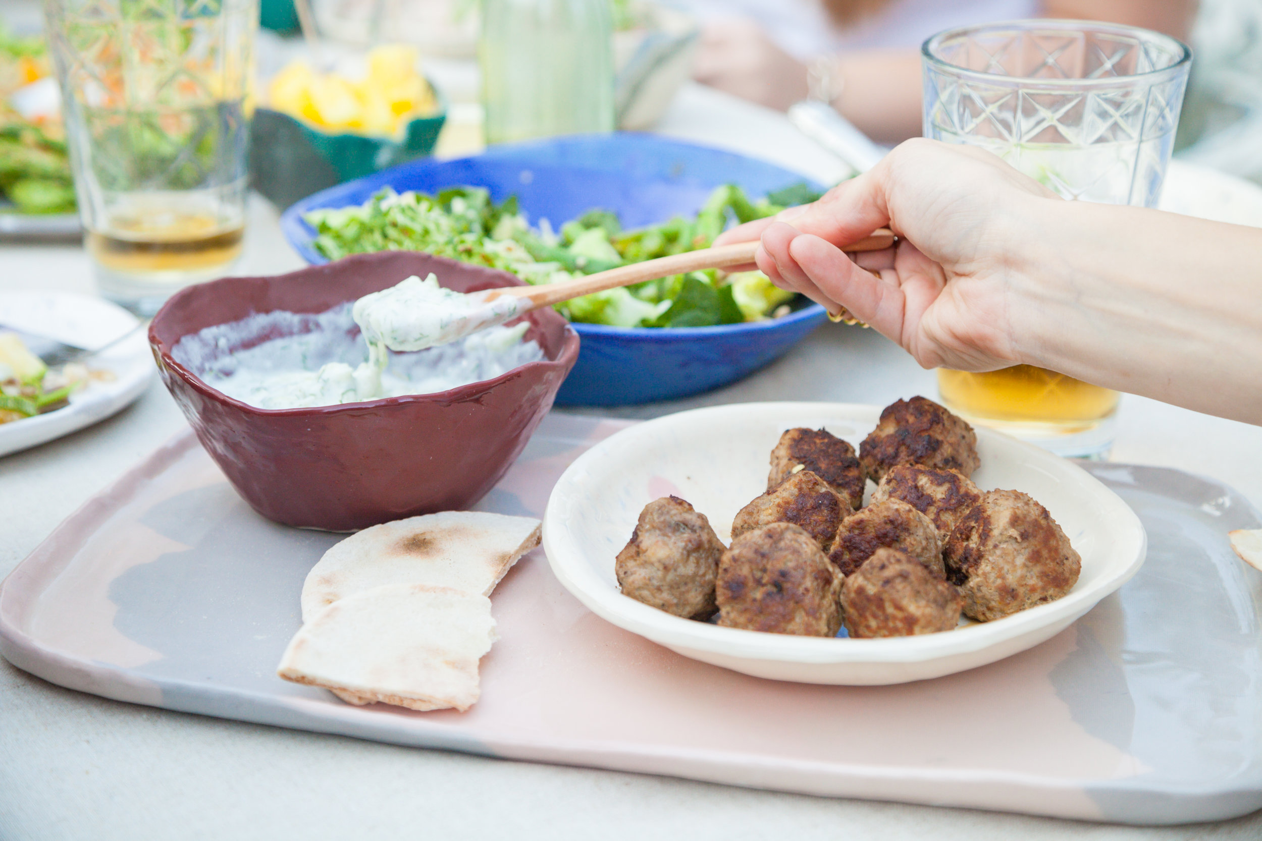Tzatziki acompañando pan pita, y bolitas de carne molida con especies y hierbas.