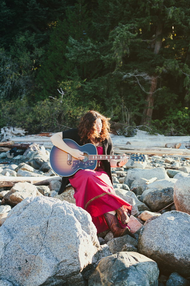 Lindsay May playing guitar on rocks at Whyte Cliff Park in West Vancouver. Photo by Rachel Pick