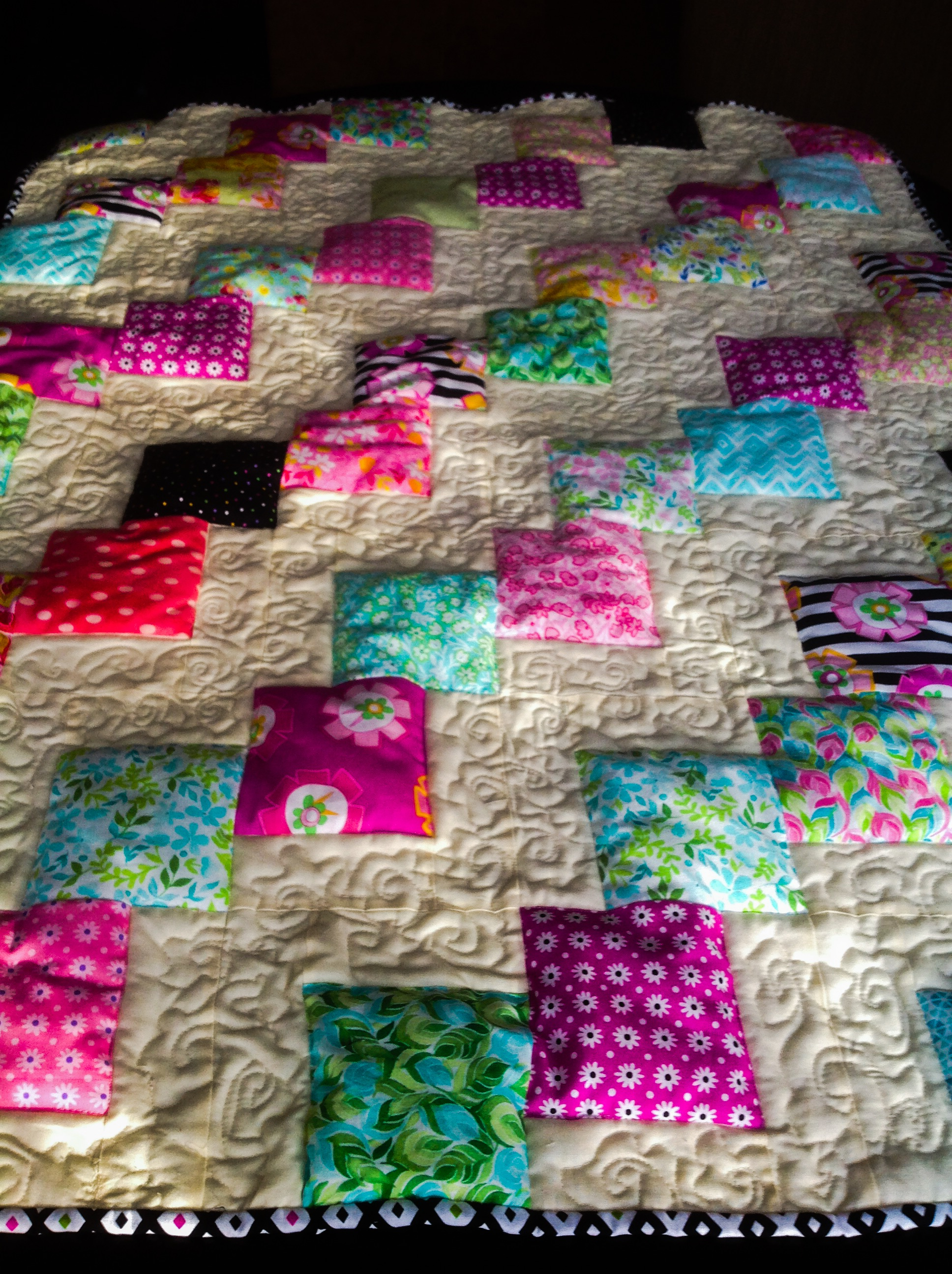 This is the front of the quilt. The background is machine quilted with a wonky swirl. I stitched in the ditch along the charms to create the 3-D effect. Also, I used a high loft batting.