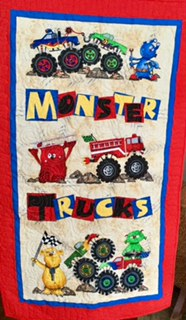 Monster Trucks  Monster Trucks is the perfect gift for the truck enthusiast in your life. It is a panel with border and binding added. The spiral quilting mimics the wheels and the border's continuous loop quilting imitates the road. It measures 28 x 46.