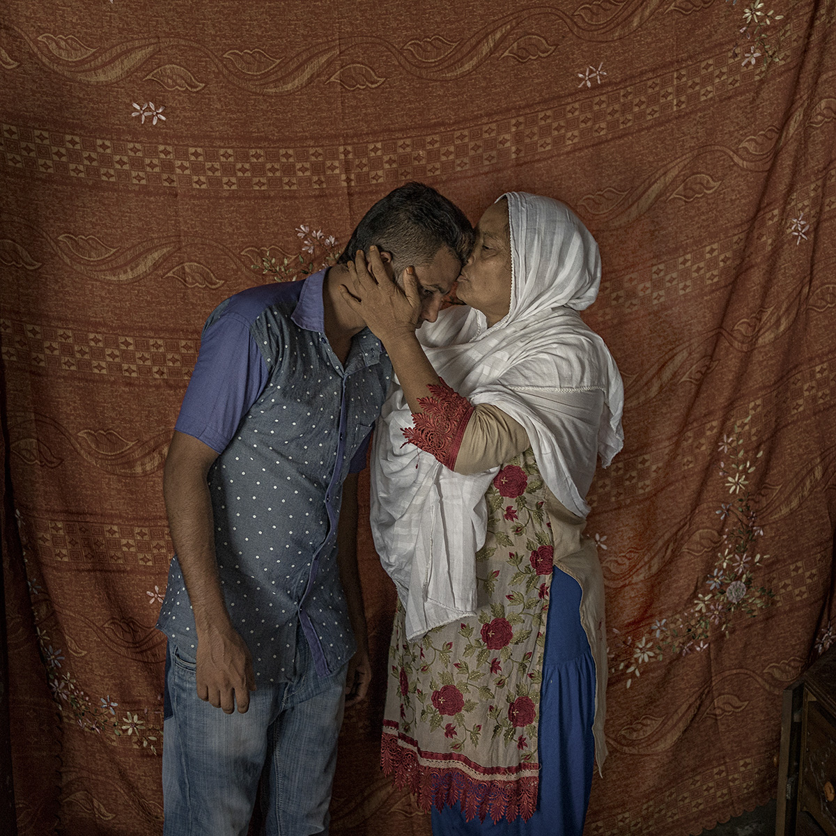 "Shobuj Hosain Ridoy (23) with his mother. He was a volunteer during the Rana Plaza Collapse. ""We heard the story about liberation war about many dead people, But didn't ever see with own eyes. But when Rana Plaza collapsed, we felt like we came into a war zone. I feel proud to take part in this battle."" His mother said."