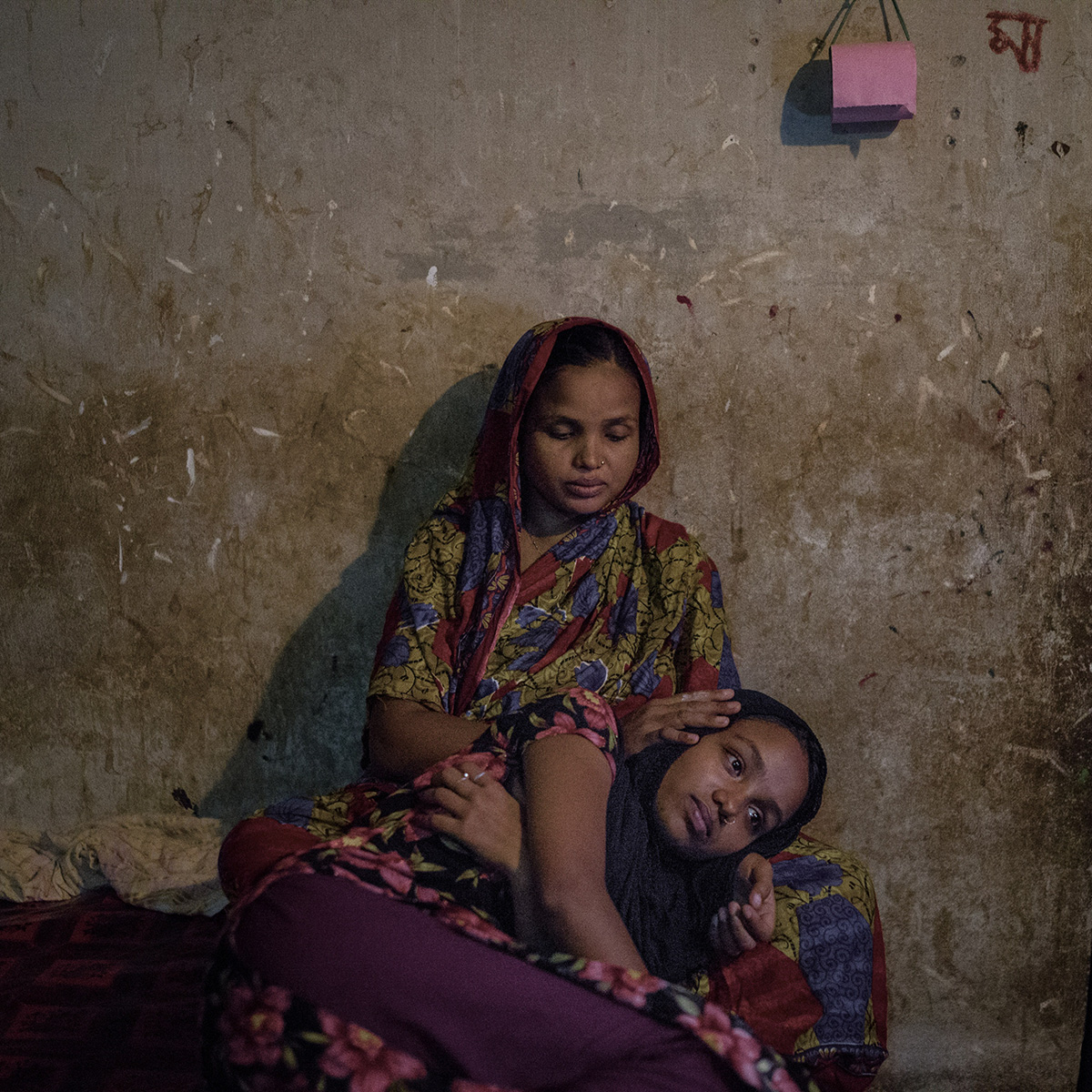 "Rabeya Khanam, a victim of Rana Plaza collapse laying on her her mother's lap. Rabeya is now 18 years old but was only sixteen at the time of the tragic incident. Her mother said, ""My two daughters were missing and like any other mother in the world, I thought I will never find her again. I was continuously praying to Allah so that I can have both my daughters back."""