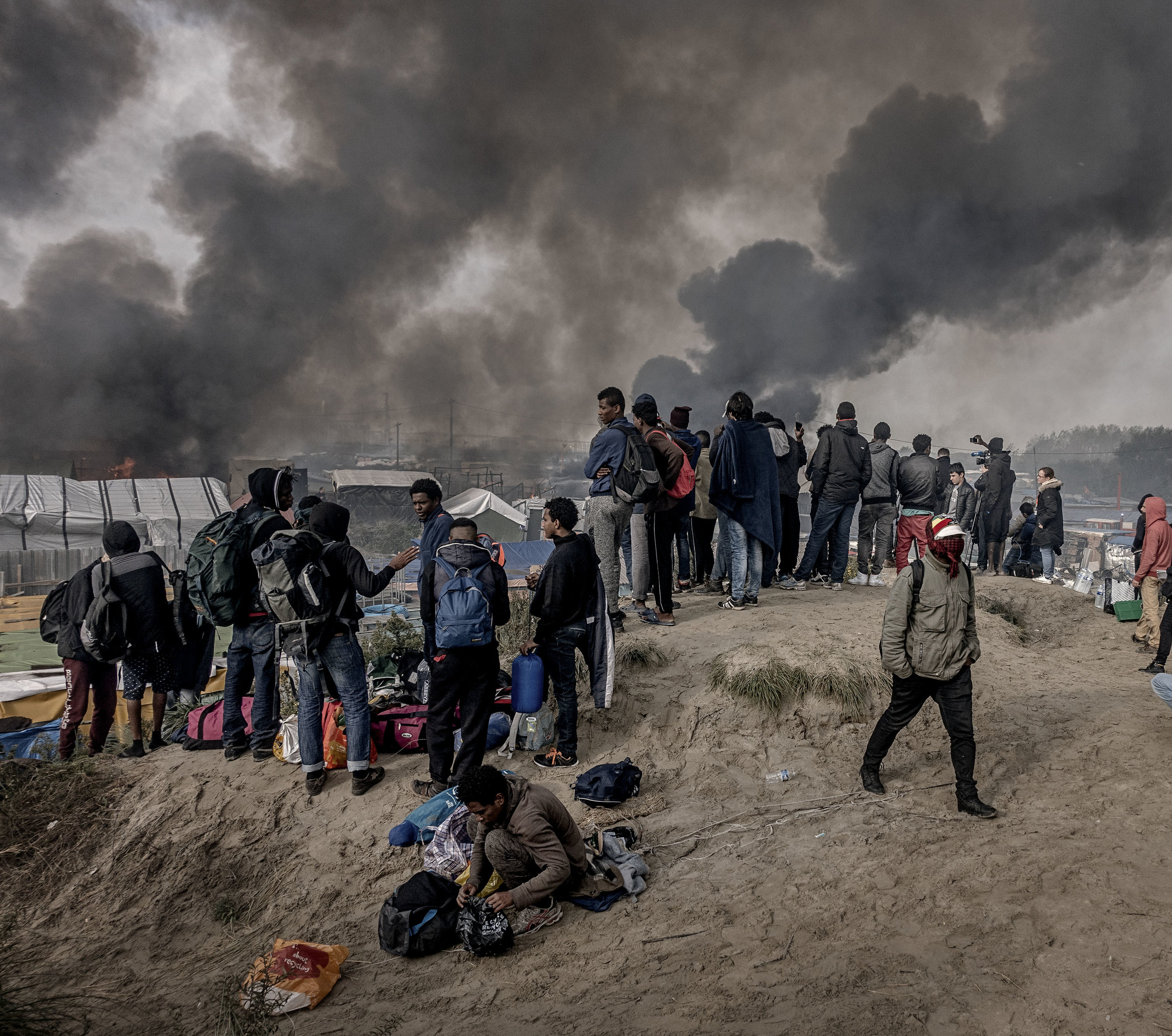26th October 2016, The Jungle of Calais in France is in huge fire. Migrants watch from the top of the hill.