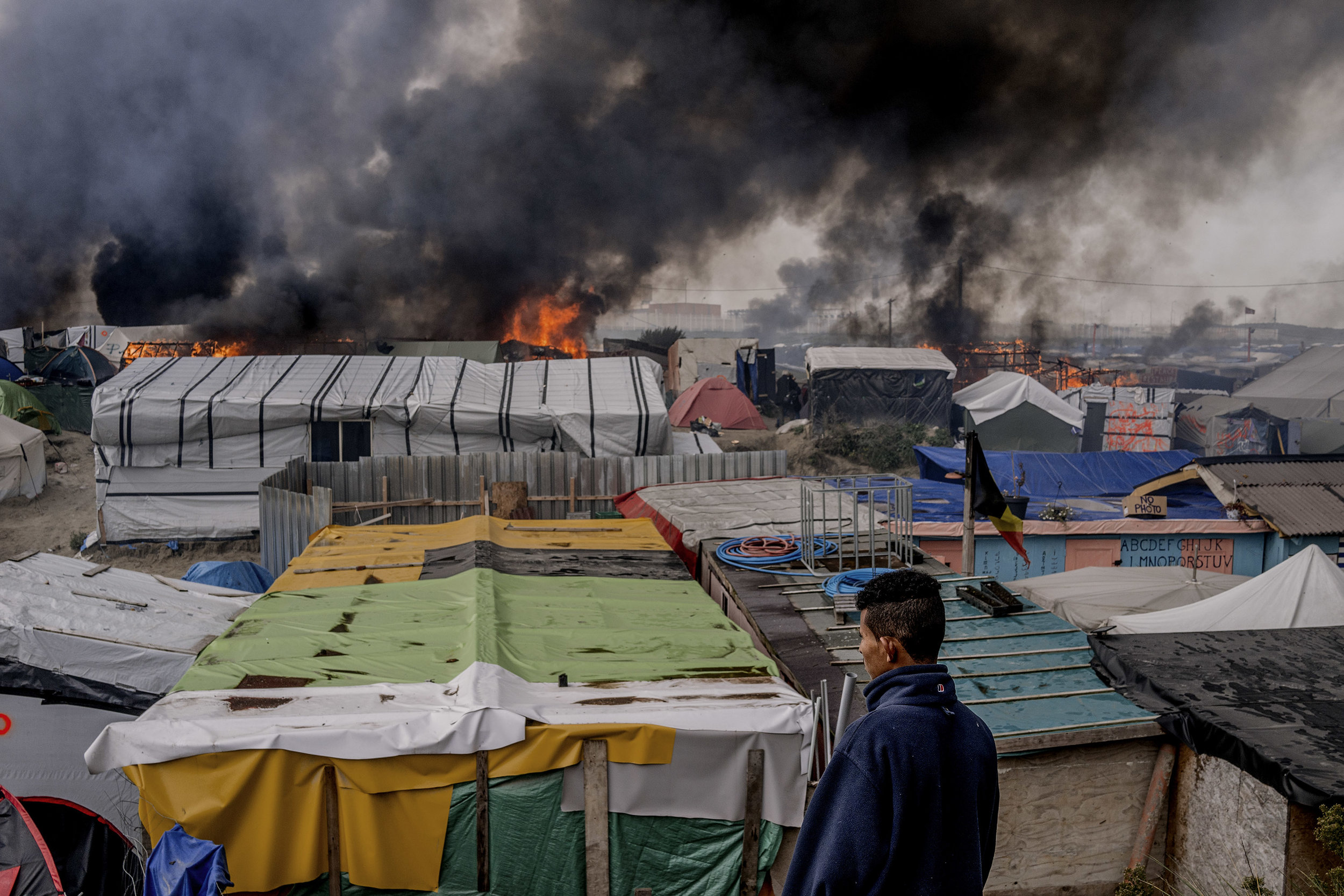 26th October 2016, The Jungle of Calais in France is in huge fire. A young migrant from Sudan watches from the hill.